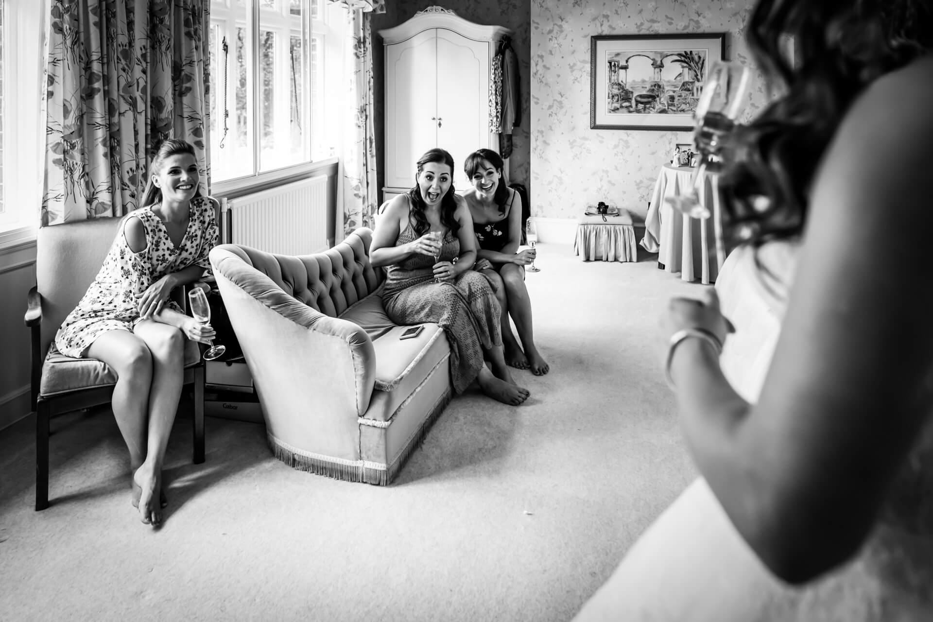 bridesmaids laughing with joy as they see the bride in her dress