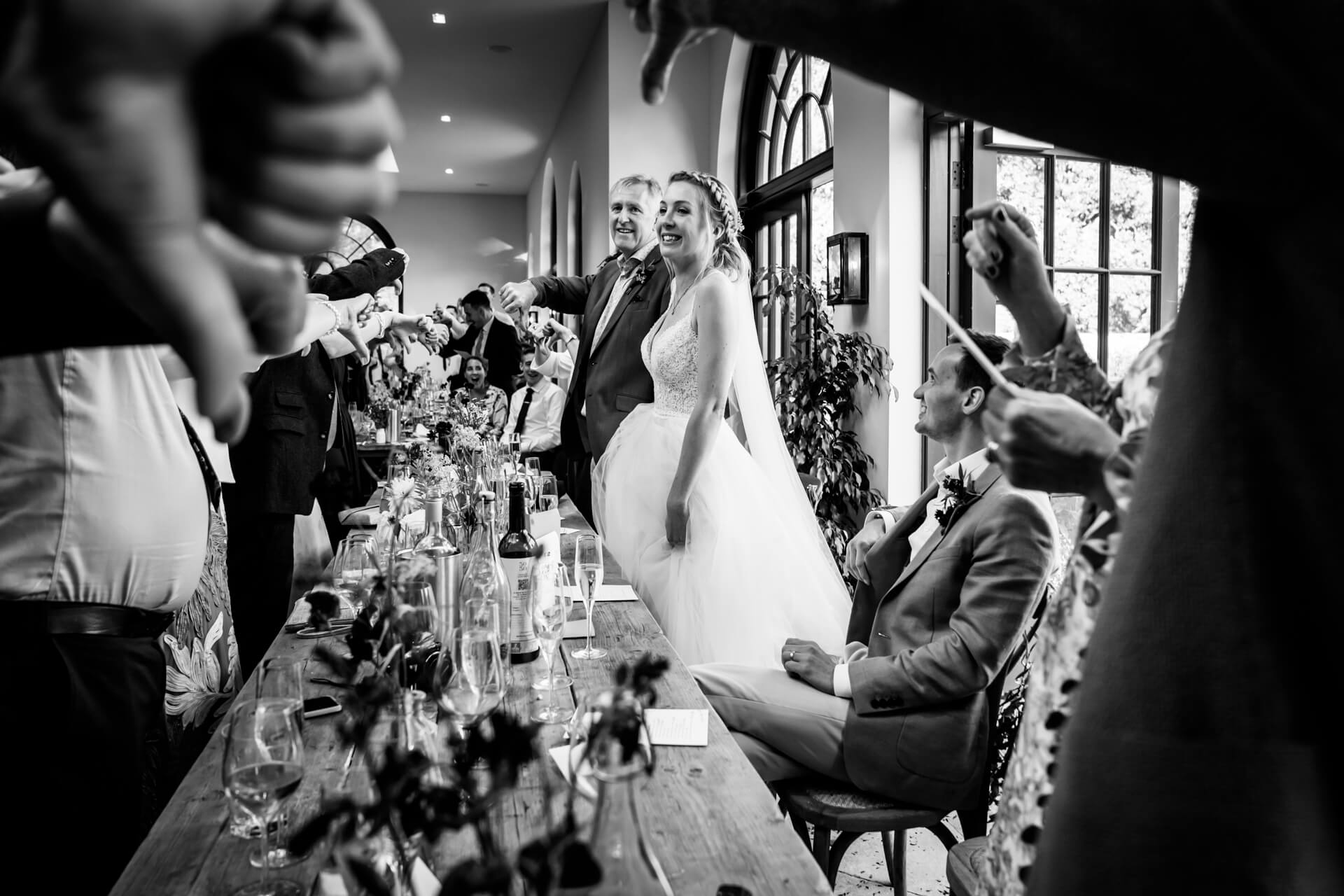 bride and her father smiling during the speeches