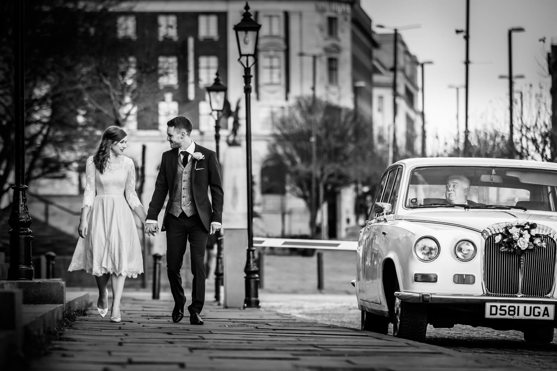 wedding couple walking along a path in Leeds whilst being watch from the wedding car by the driver
