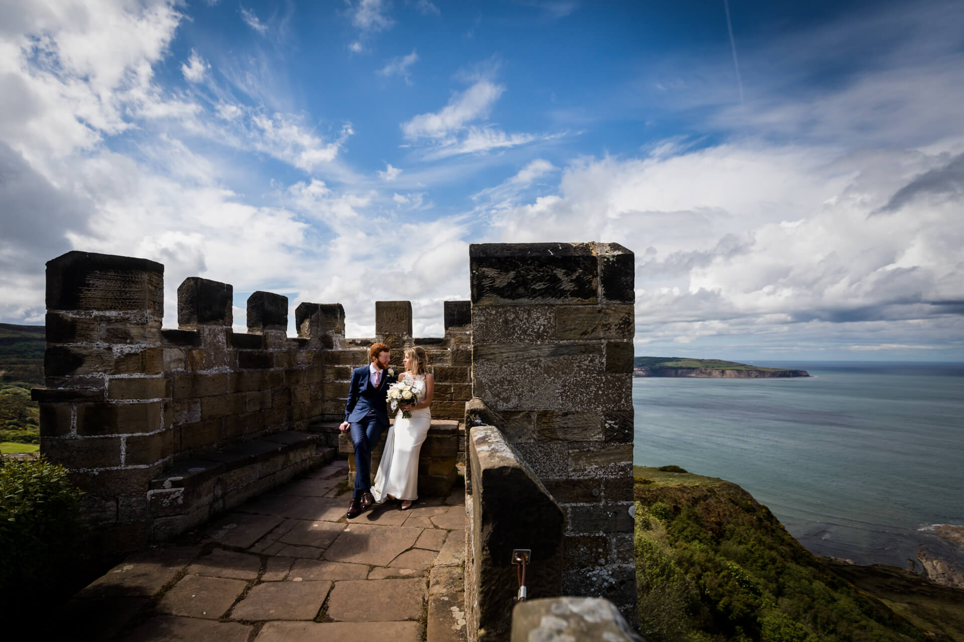 wedding couple sitting in the castle ruins at Raven hall