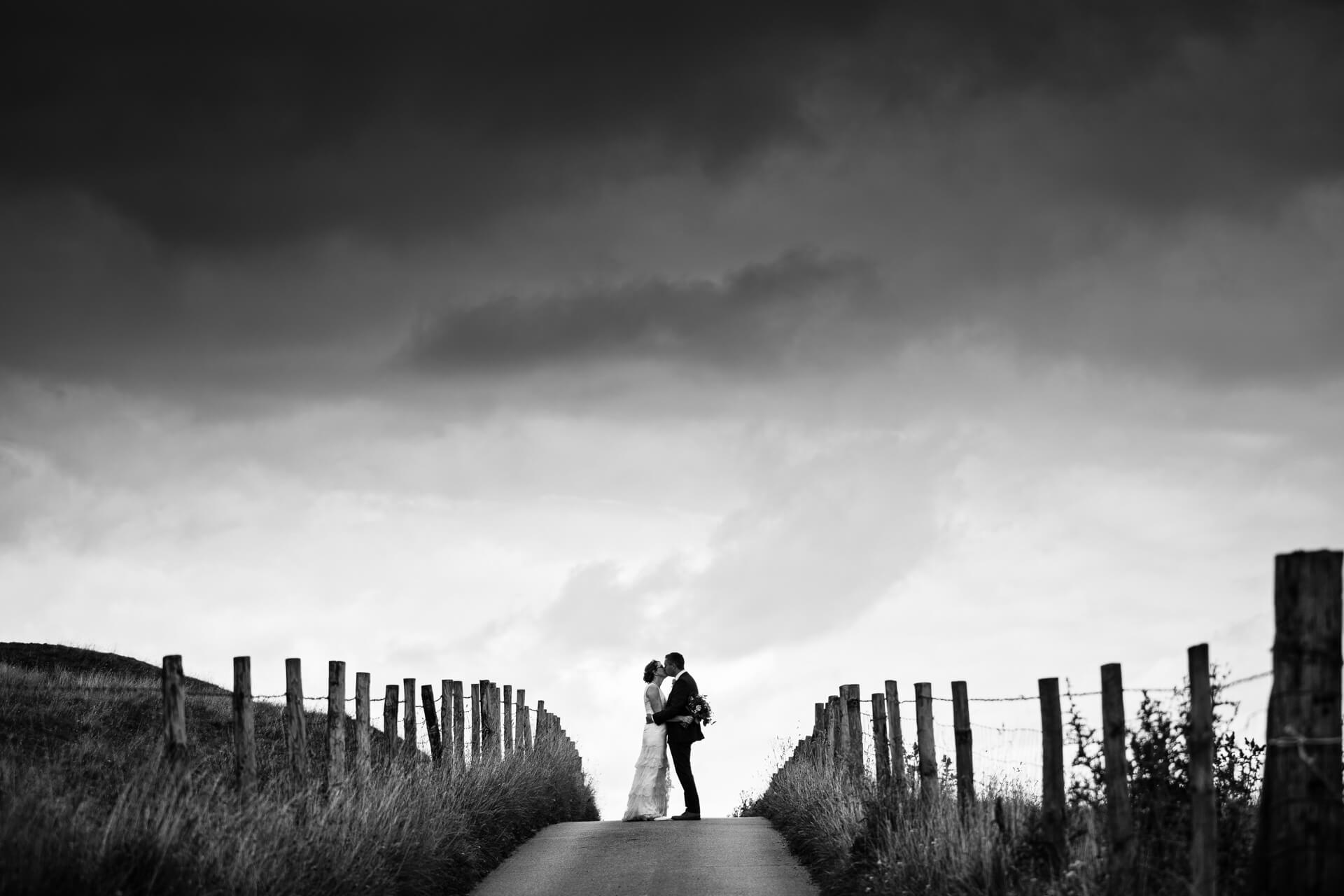 wedding couple kissing at the top of a hill