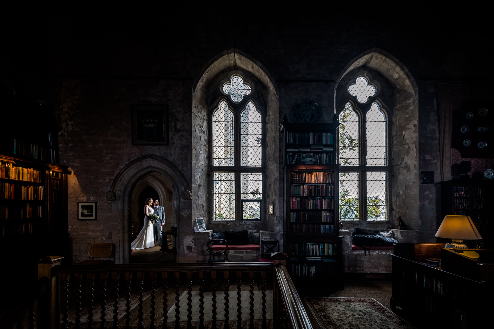 wedding couple looking through a window of an old Manor House