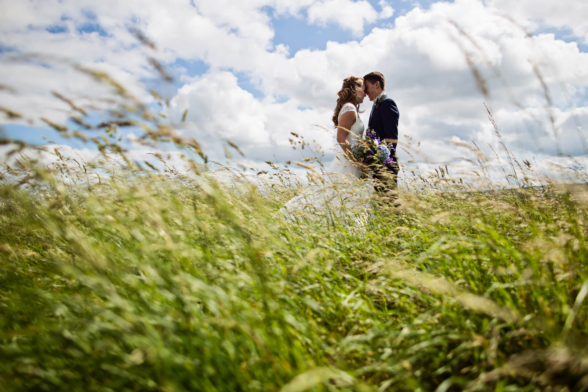 wedding couple standing together isn some long grass
