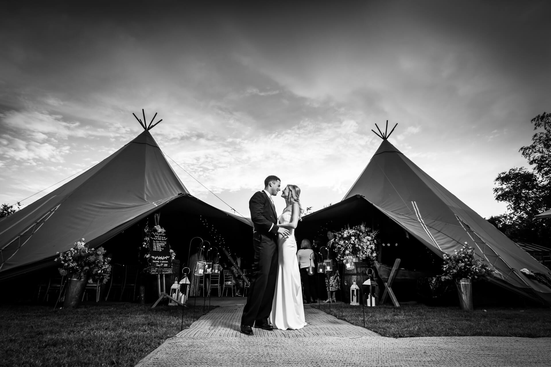 bride and groom standing together in front of a tipi
