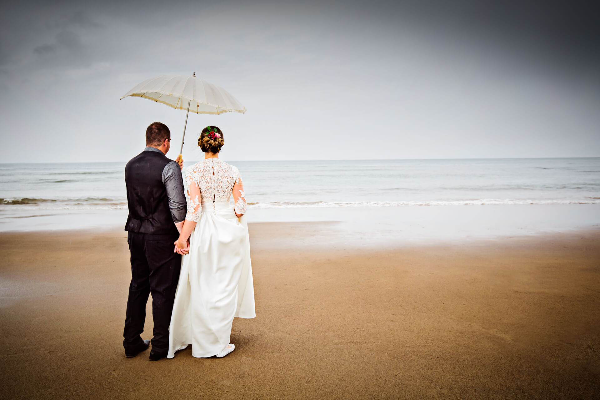 bride and groom standing on a beach and looking out to sea