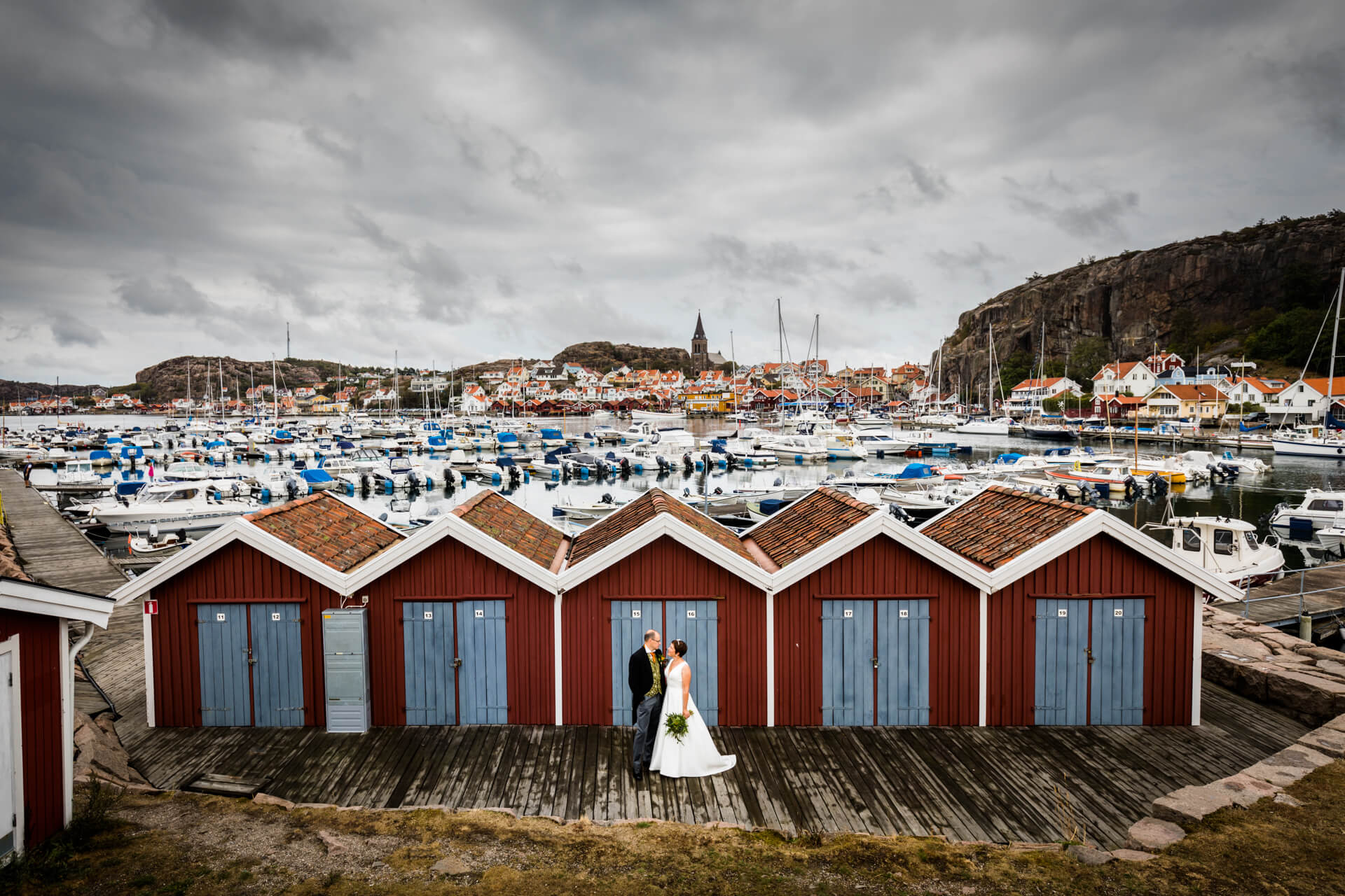 bride and groom standing in front of some Swedish fishing huts