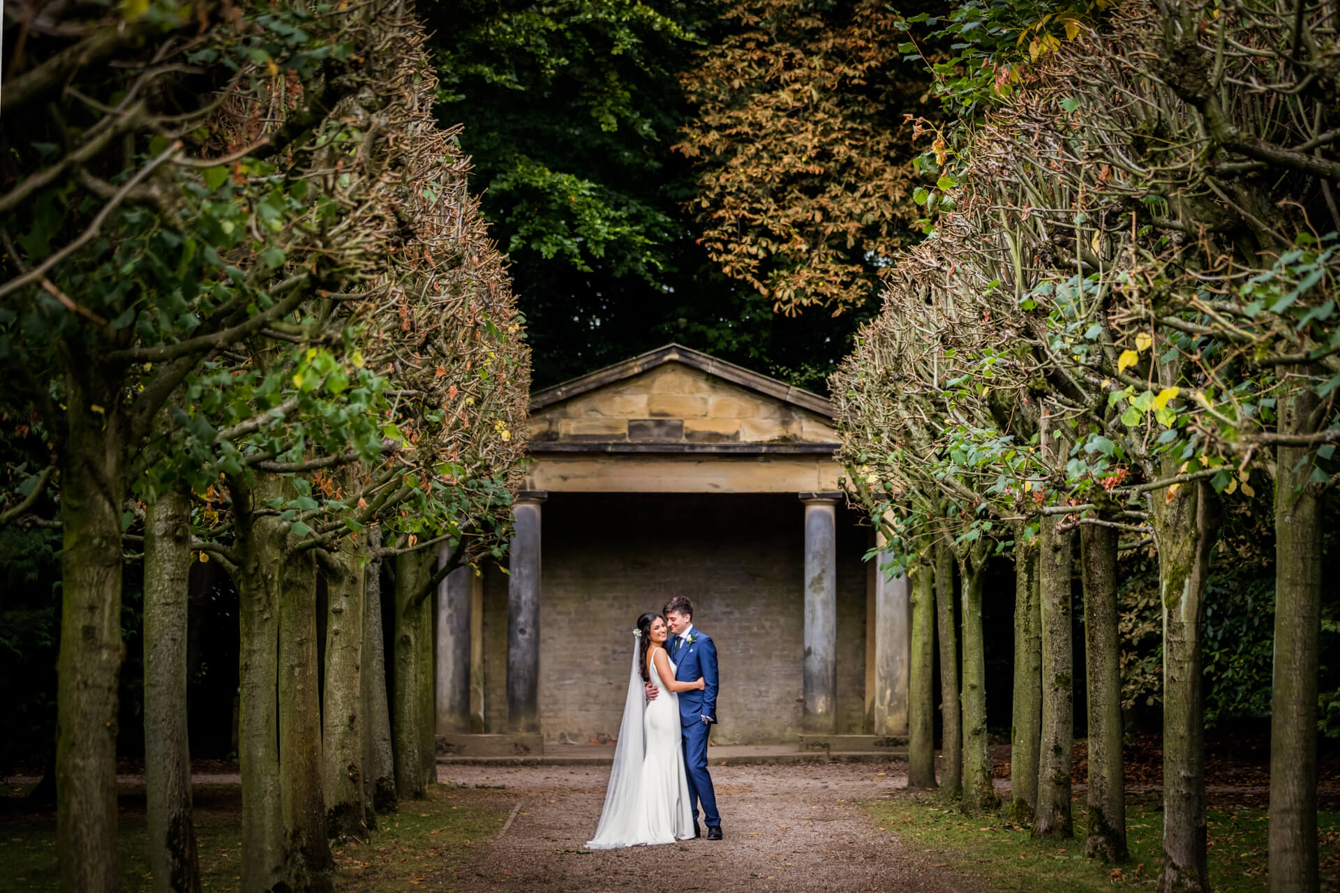 wedding couple hugging in between a tunnel of tall trees