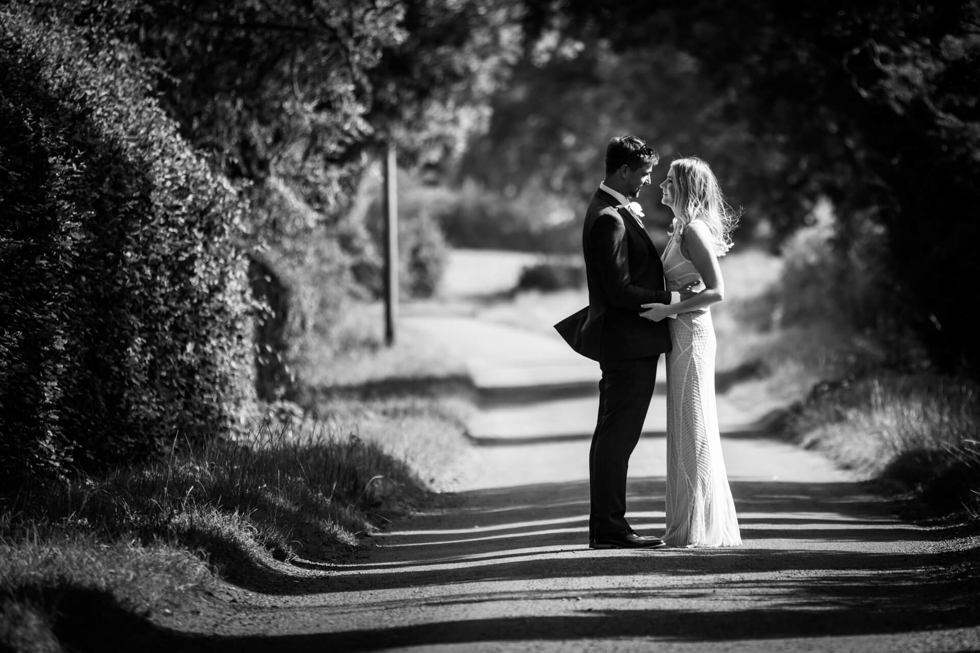 wedding couple standing together on a countryside lane