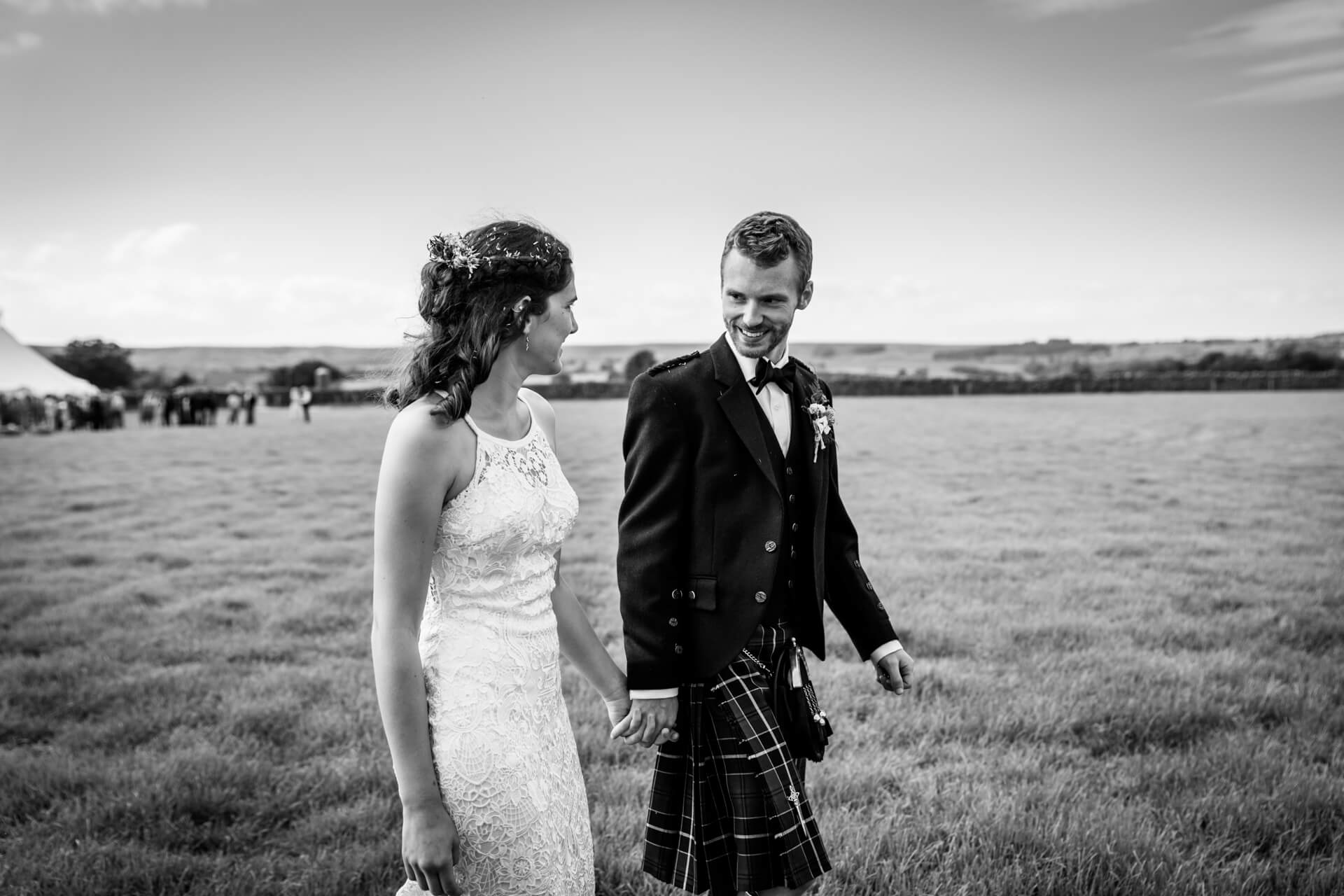 wedding couple walking hand in hand in a field