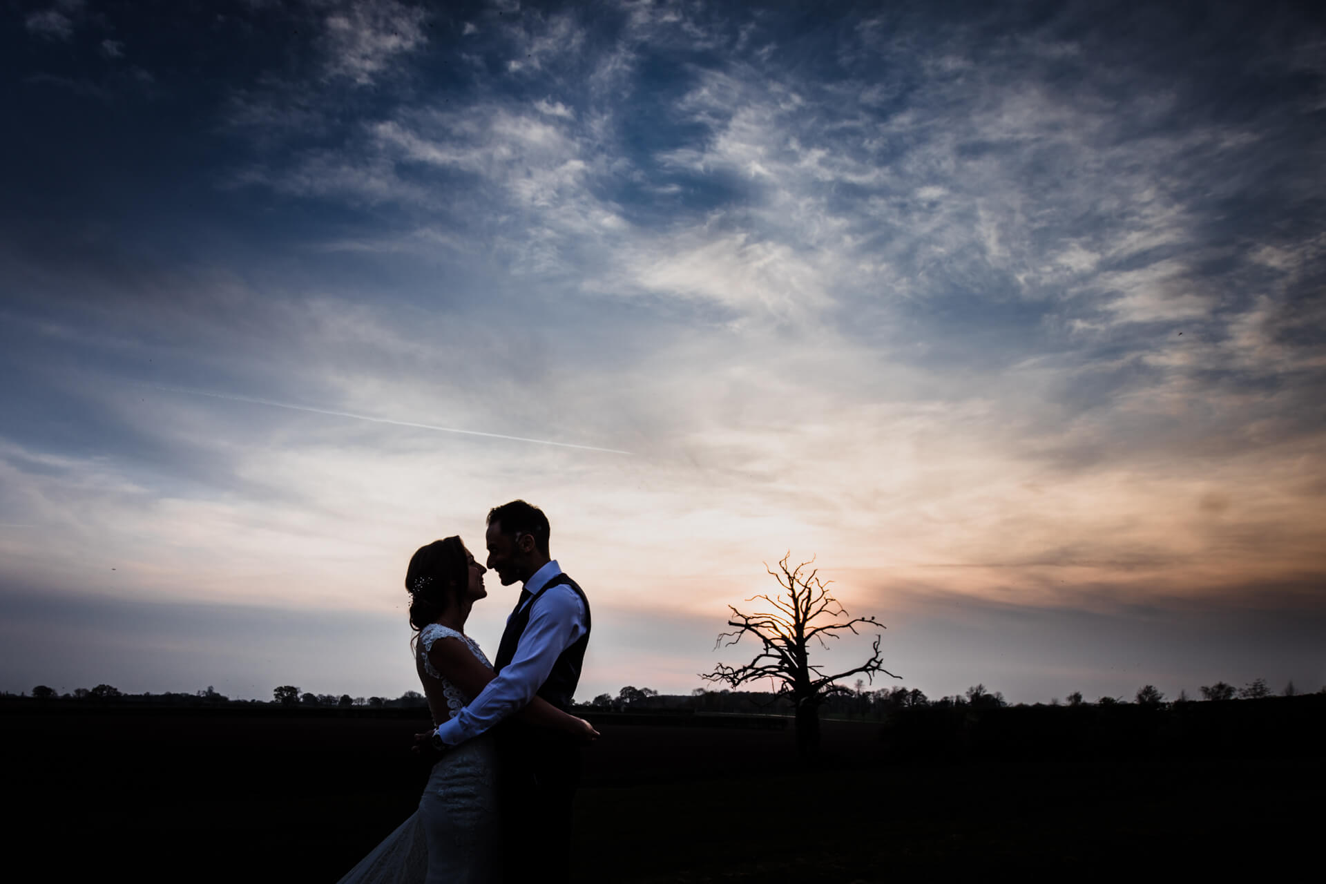 silhouette of a couple about to kiss in front of a sunset
