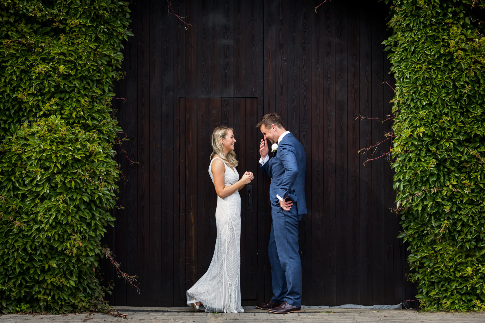 wedding couple laughing together in front of a wedding barn door