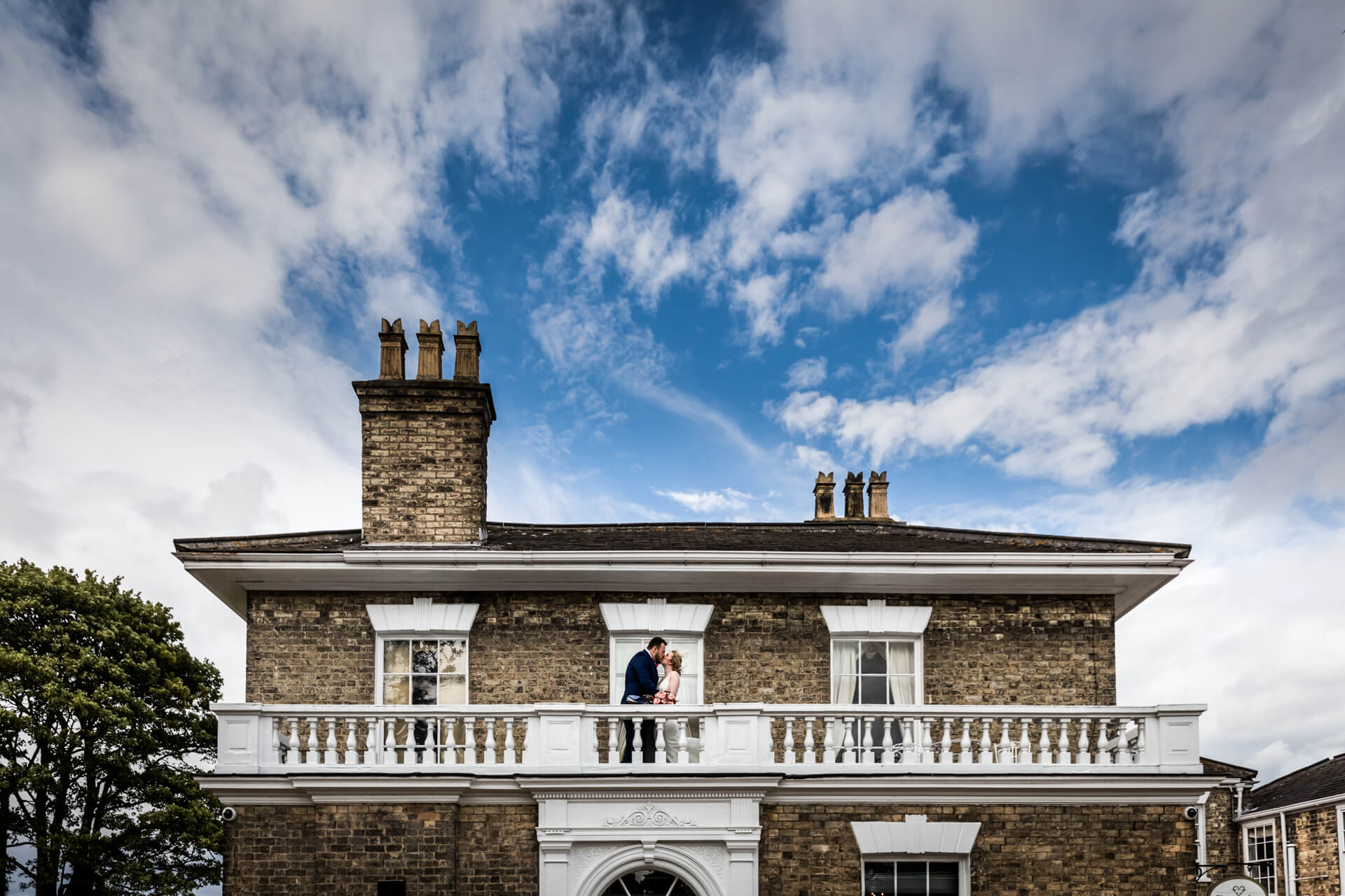 bride and groom kissing on a balcony at Dunedin House