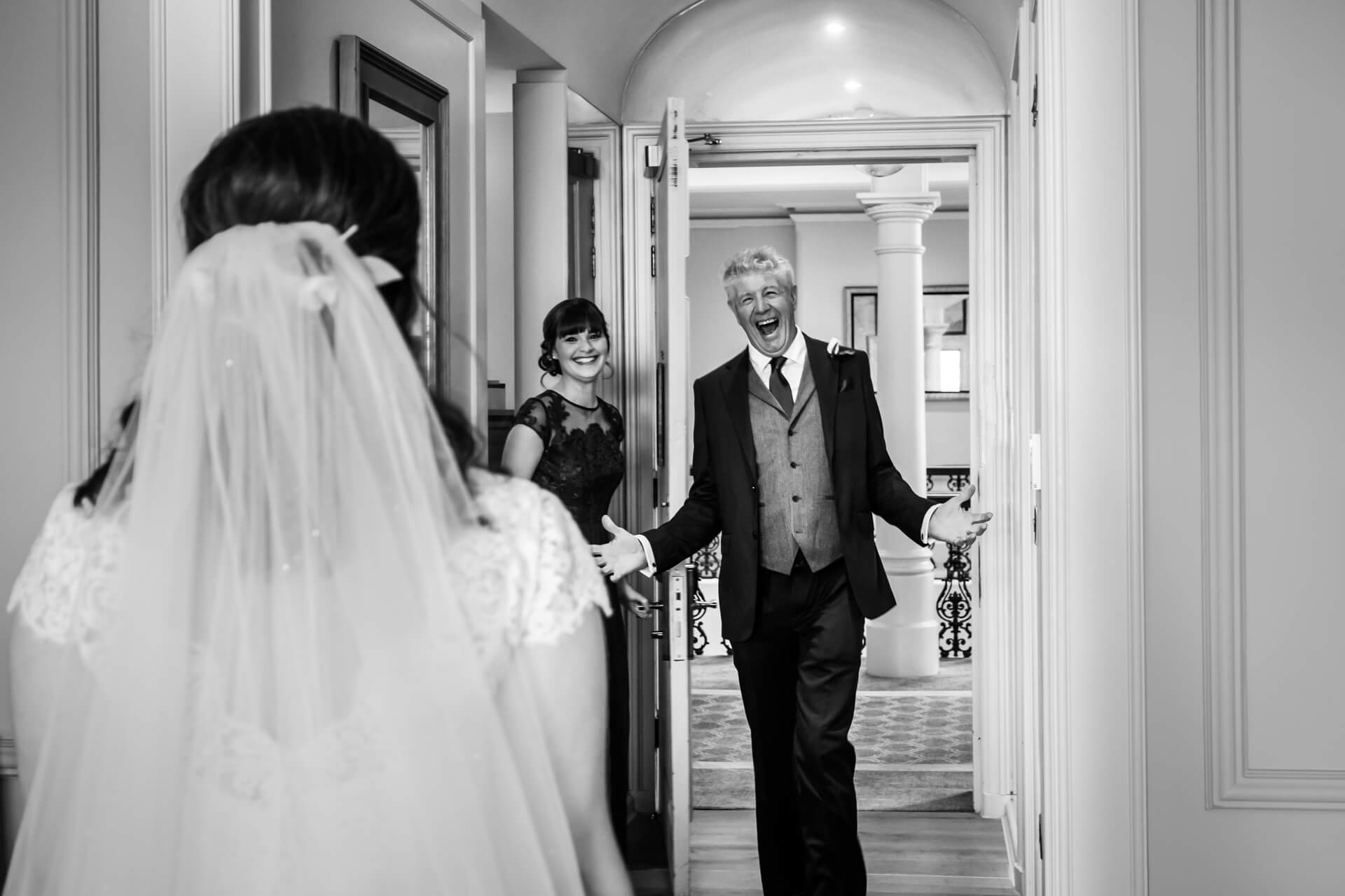 father of the bride laughing with delight as he sees the bride for the first time