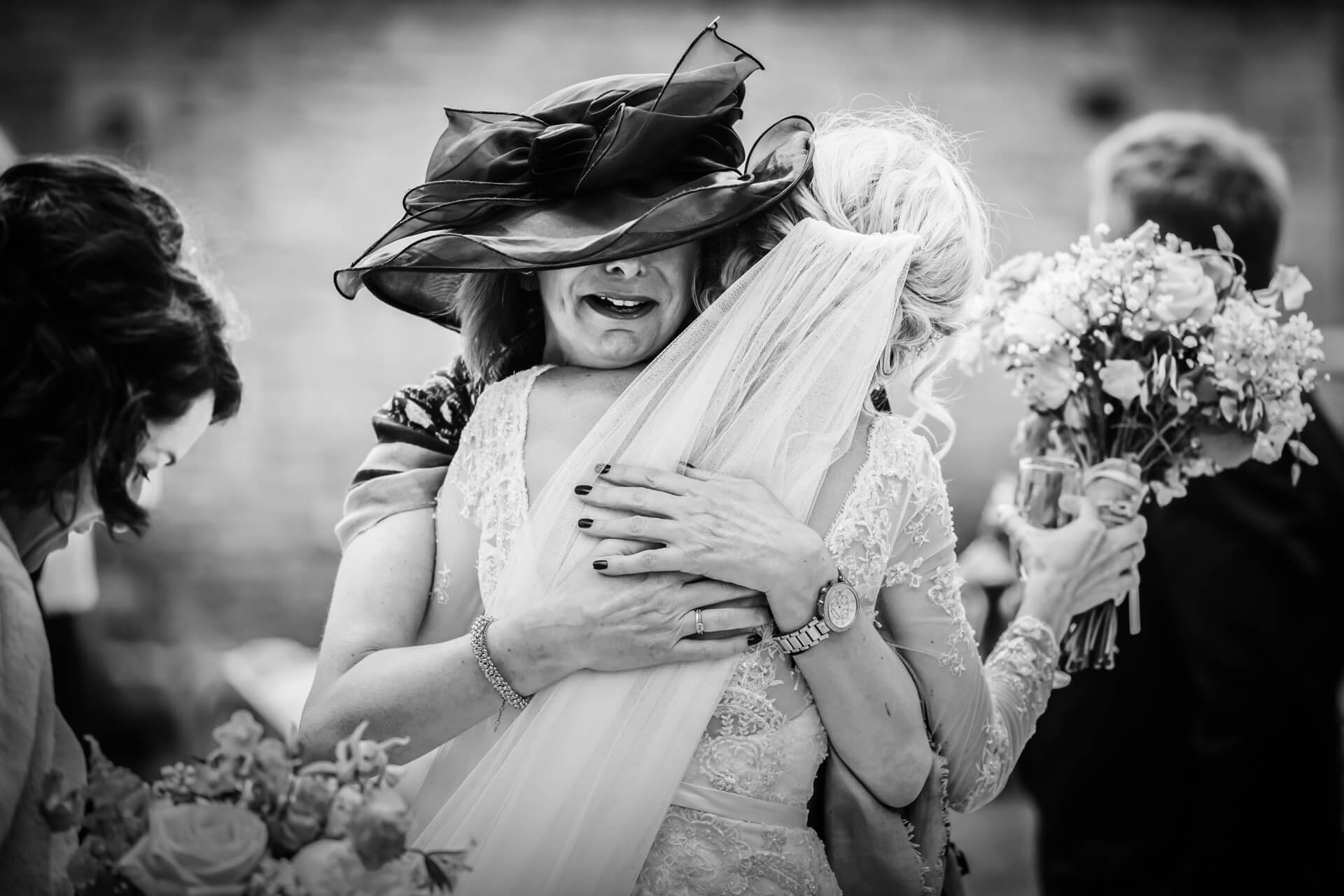 brides friend hugging the bride and smiling
