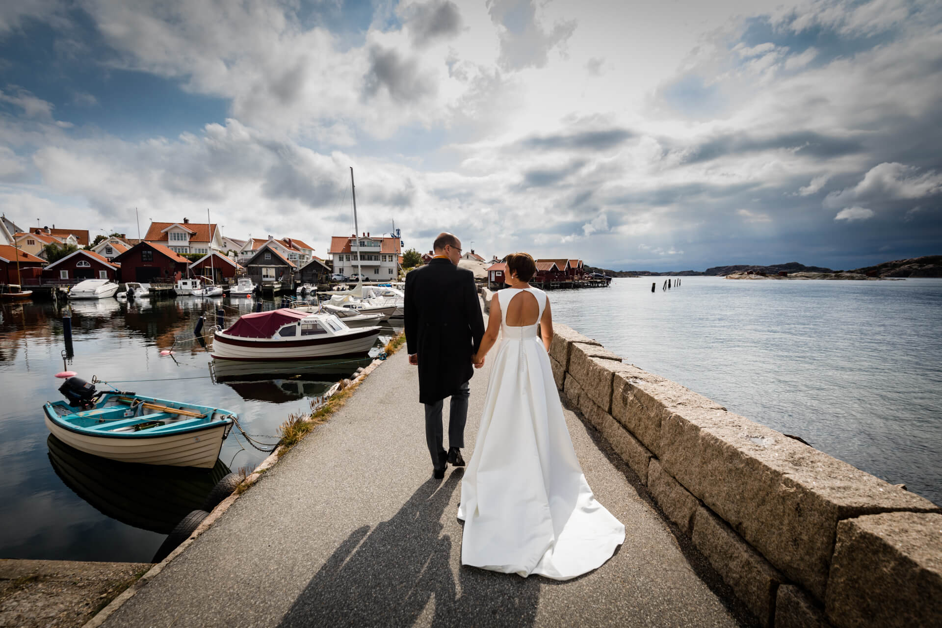 bride and groom walking along a coastal path in Sweden