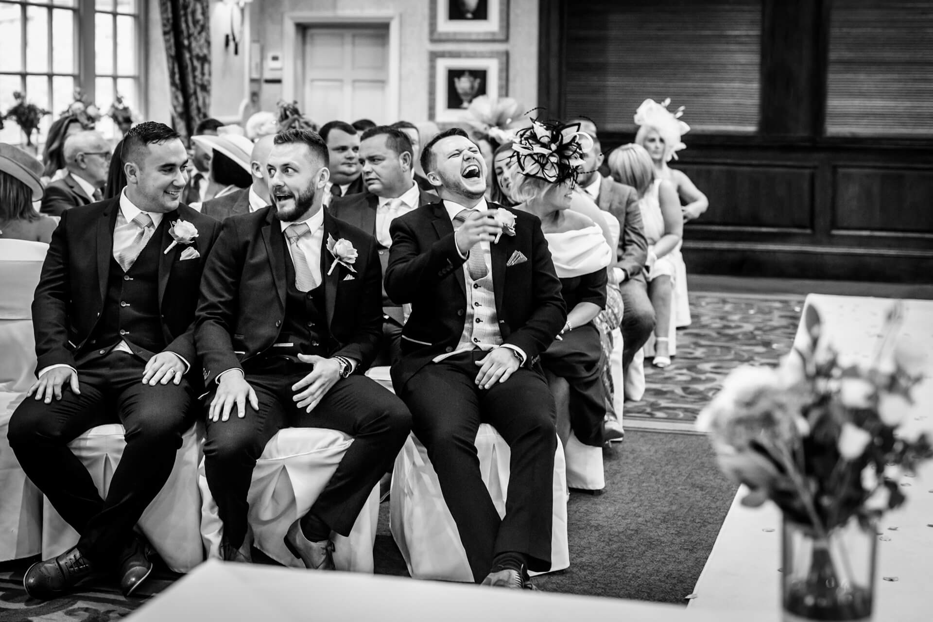 groomsmen laughing whilst sitting in the ceremony room