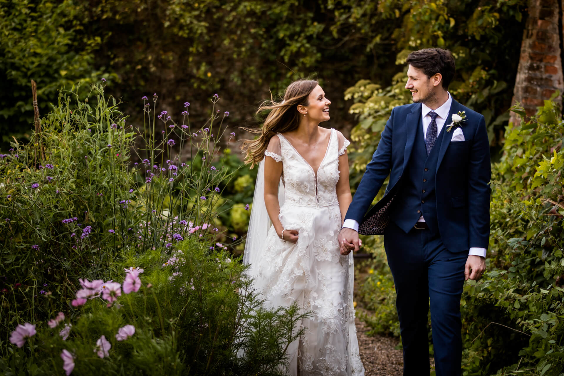 bride and groom walking in the gardens at Saltmarshe Hall