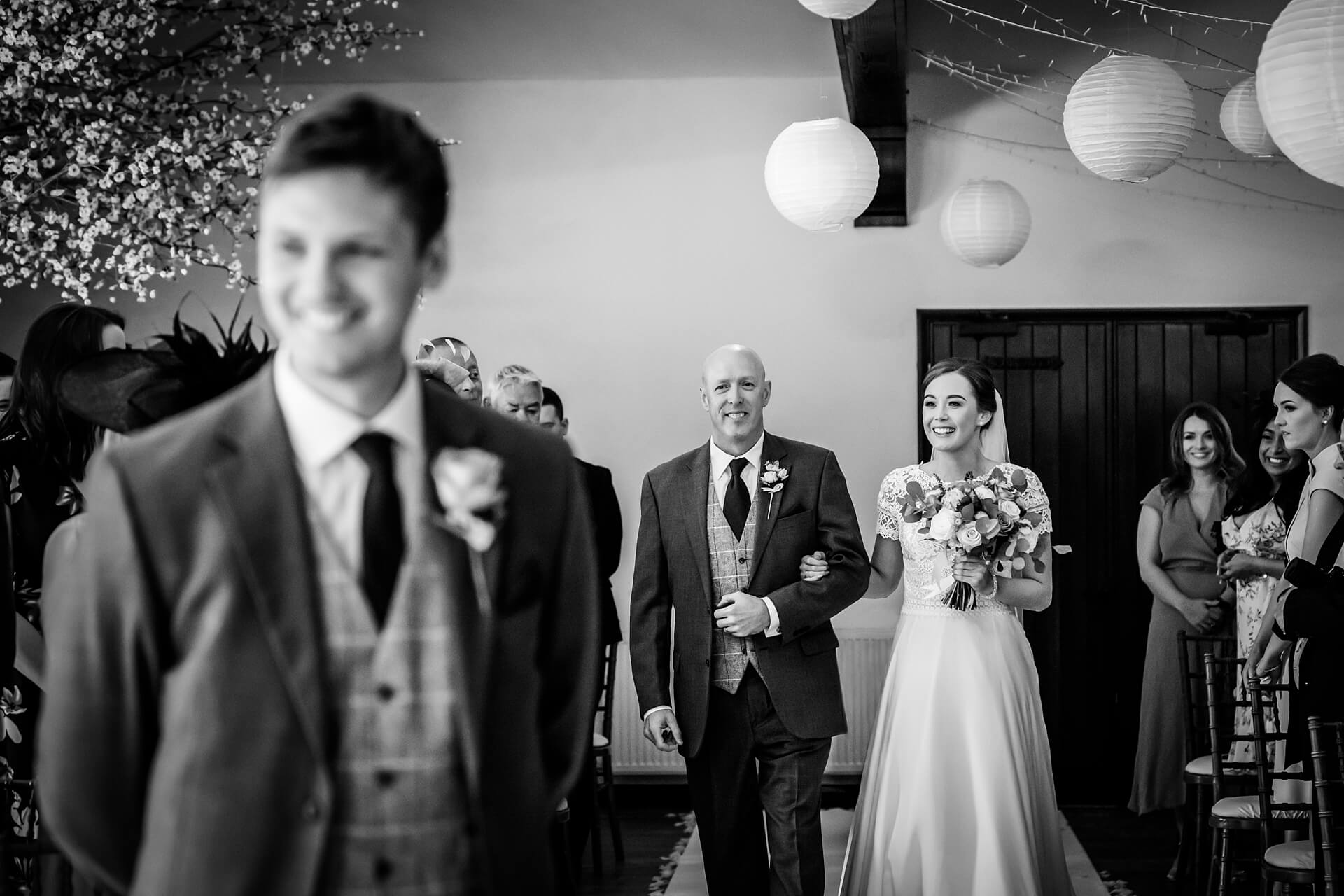 groom smiling as the bride and her father walk down the aisle