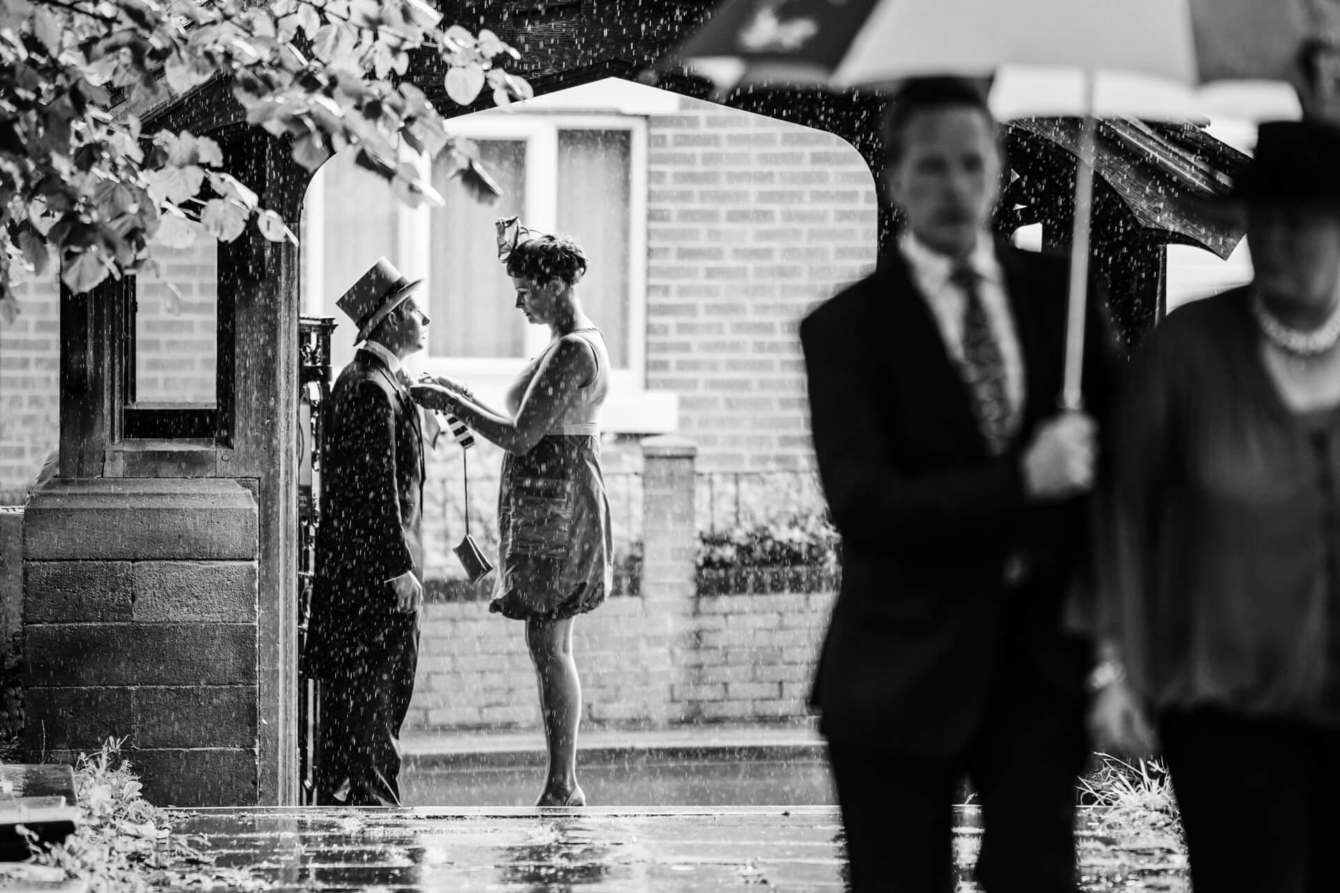 bridesmaid fixing a groomsman tie under a church arch in the rain