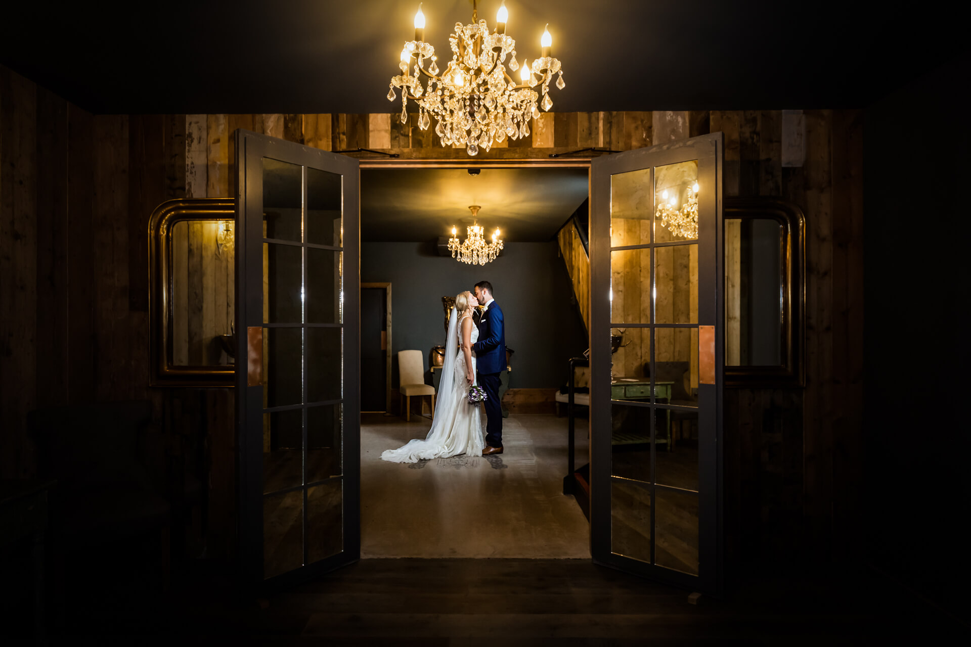 bride and groom kissing under a chandelier at Wharfedale Grange