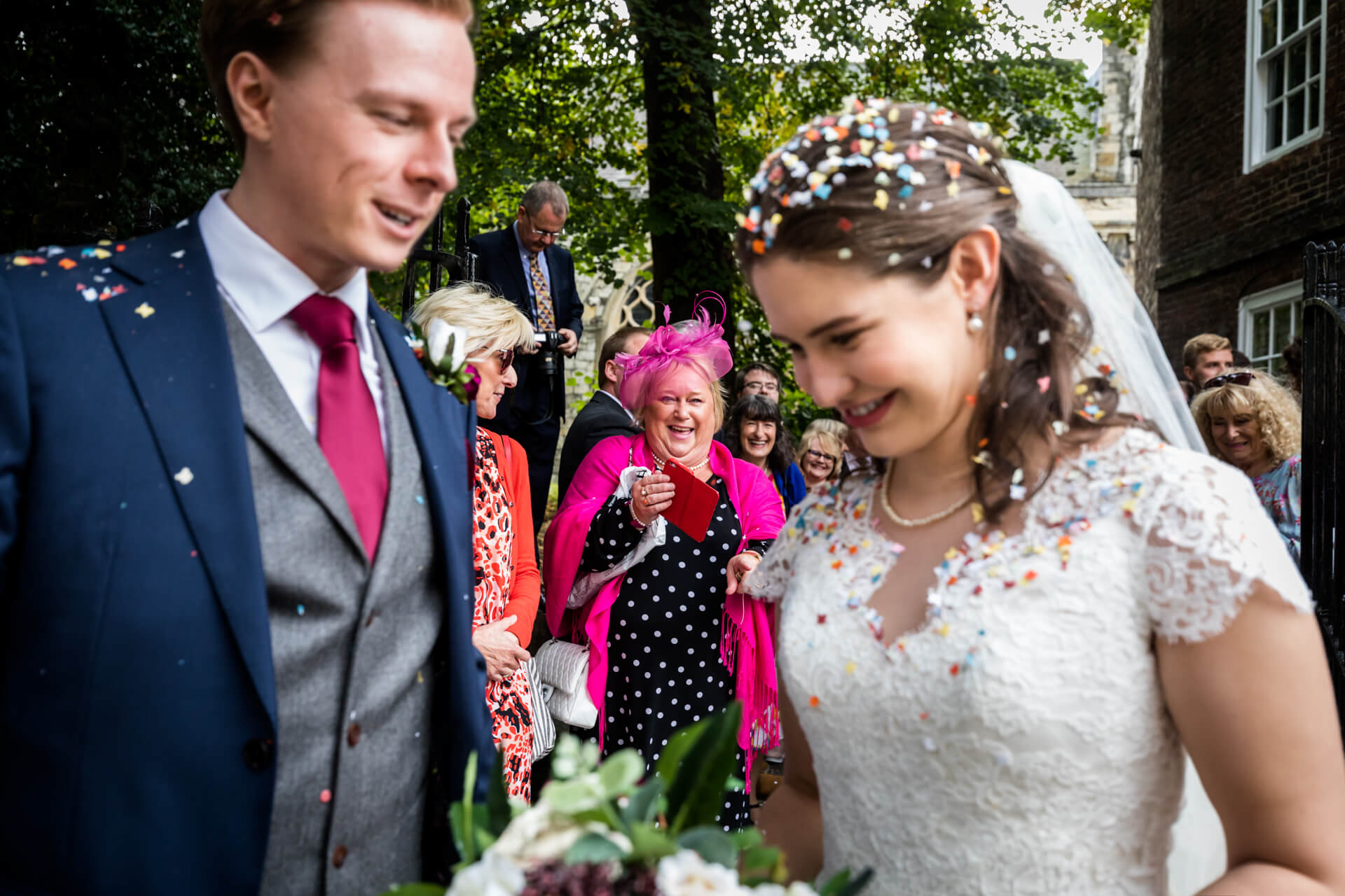 guest laughing at the bride and groom who are covered in confetti