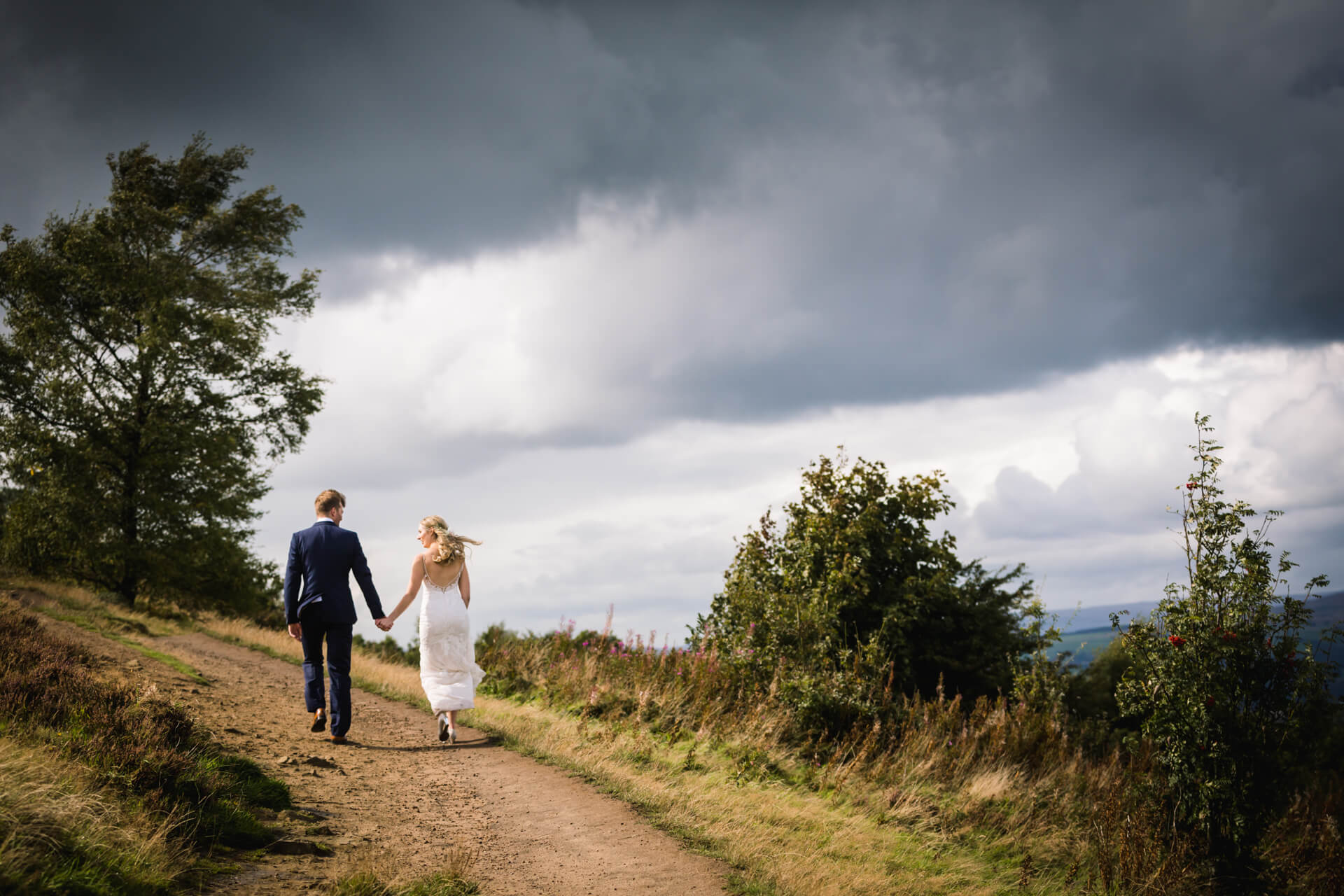 bride and groom walking up a hill at Otley Chevin