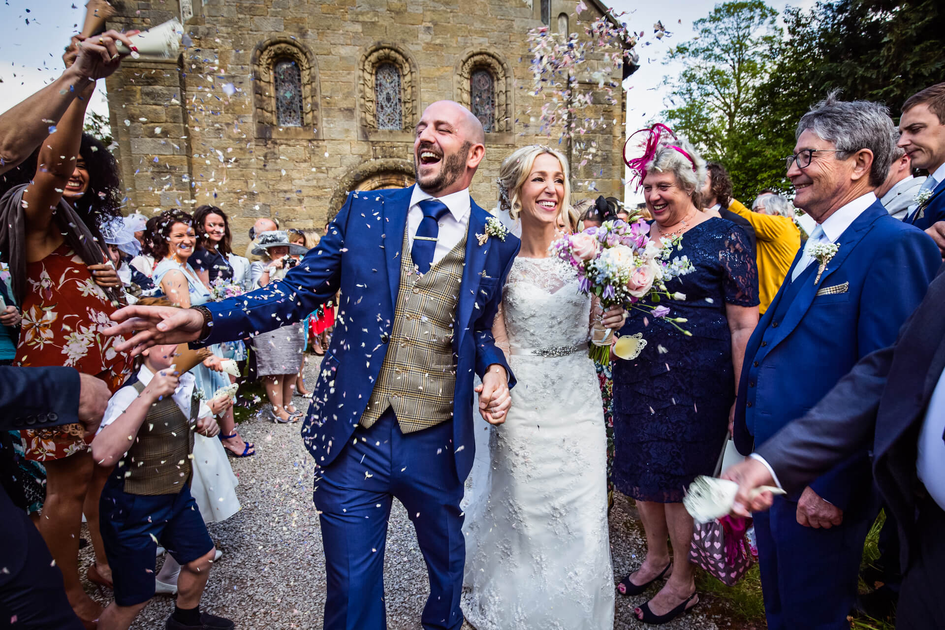 bride and groom being showered with confetti outside a Lake District church