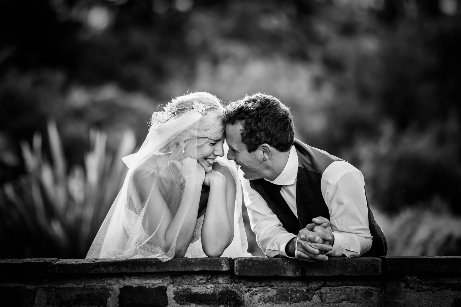 bride and groom leaning on a wall and laughing together