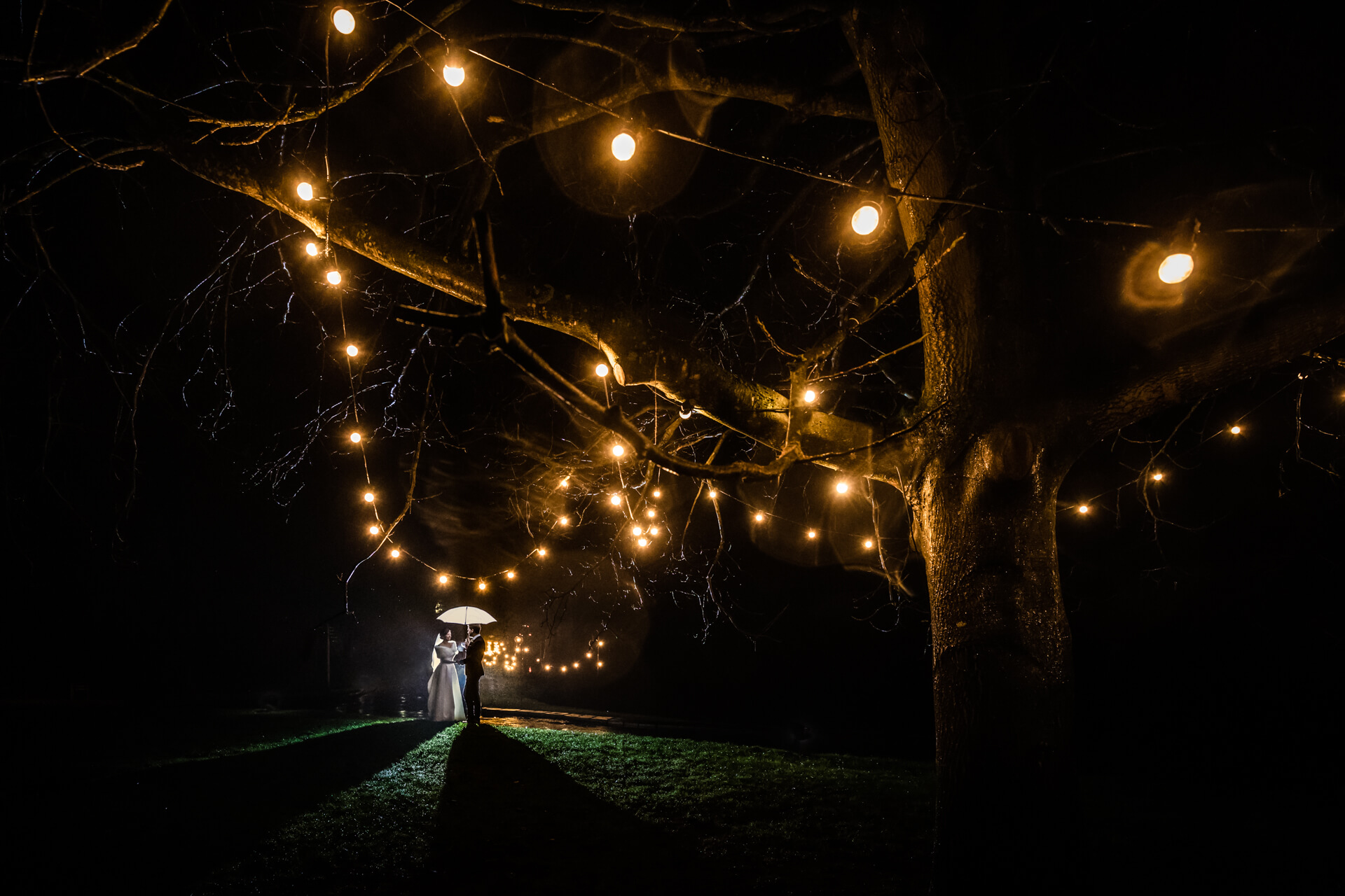 nigh time portrait of the wedding couple under some fairy lights at East riddles den hall