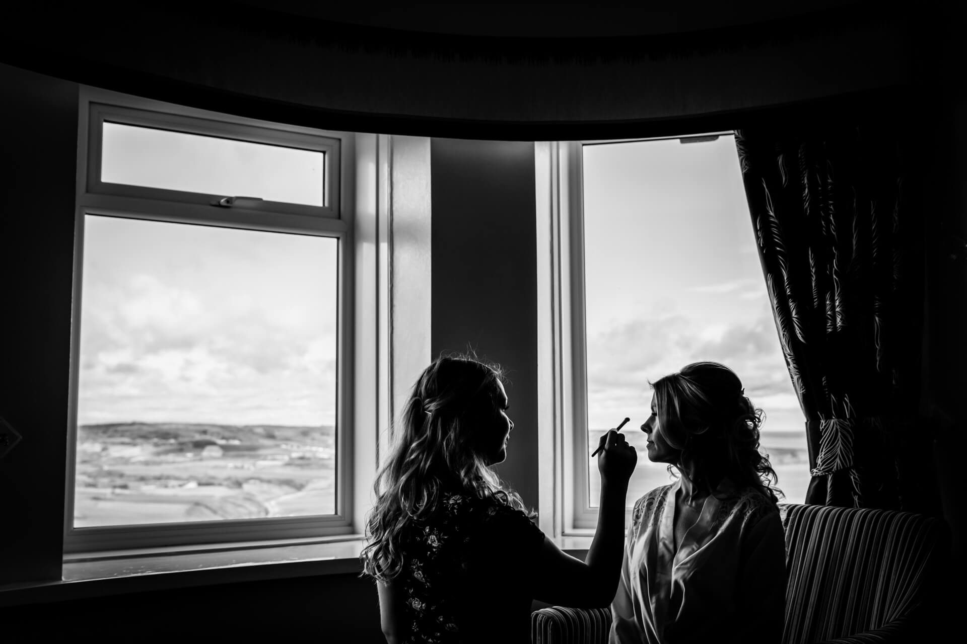 bride having her makeup done in front of a window with a view