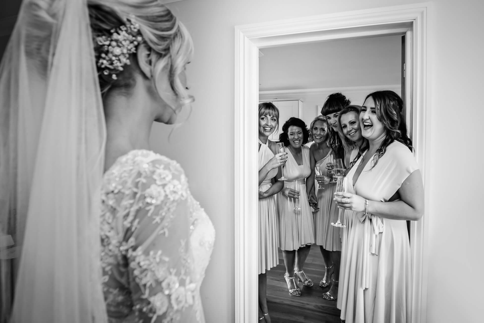 bridesmaids all smiling when they see the bride in her dress