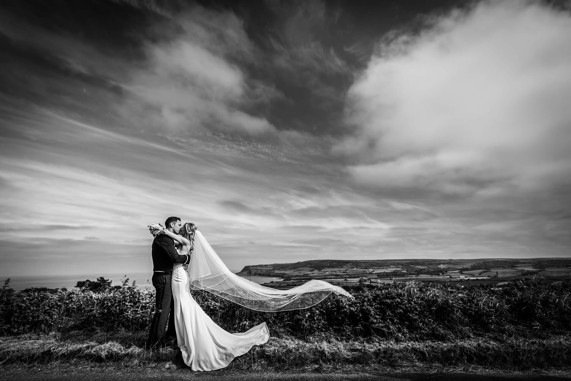 groom kissing the bride on a hill top overlooking Whitby