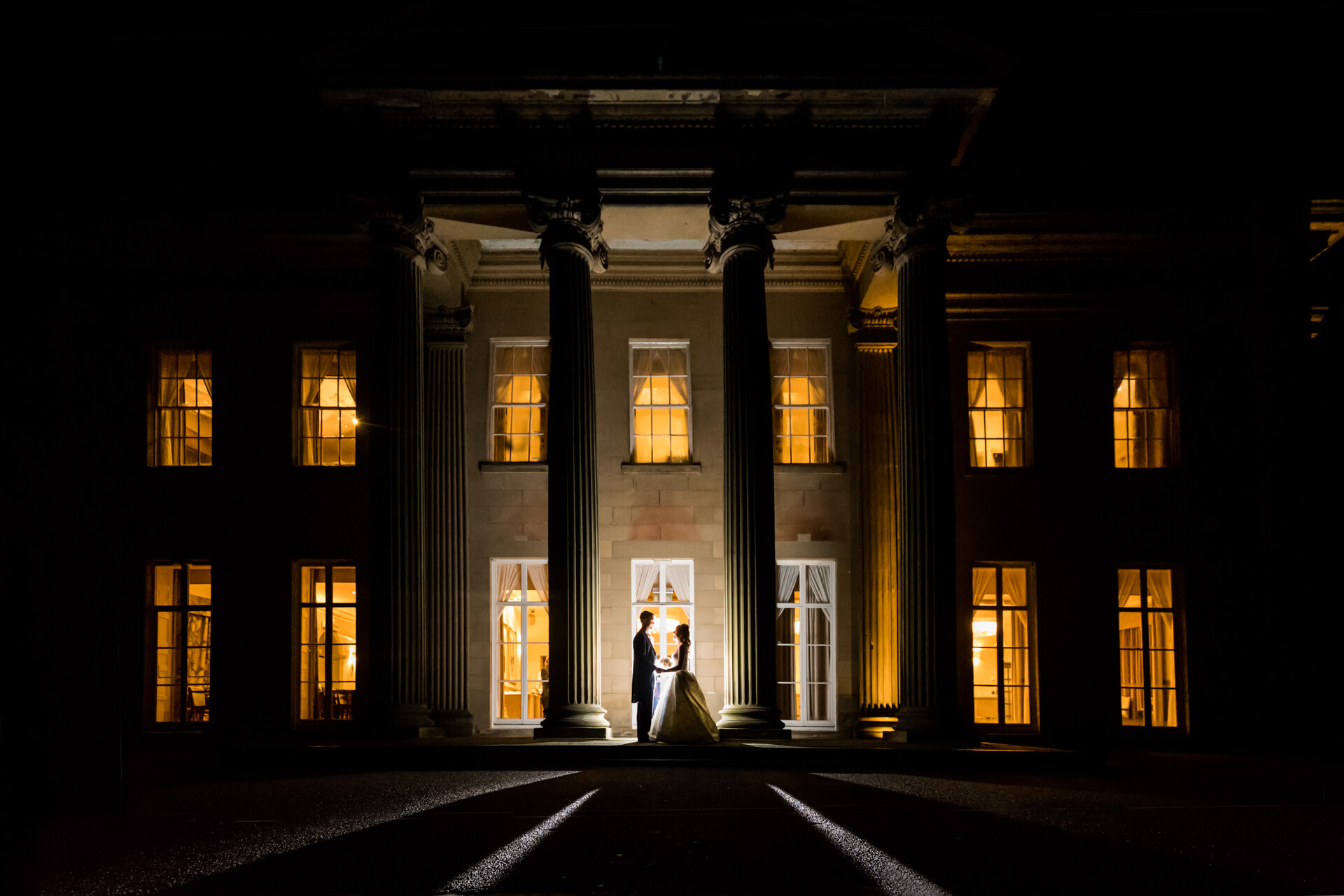 nighttime portrait of the bride and groom holding hands in front of a wedding mansion