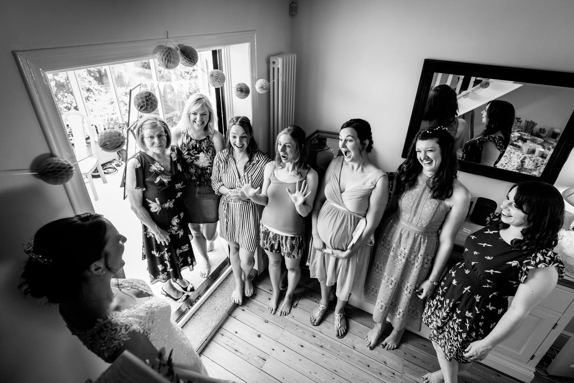 the bridal party shrieking with delight upon seeing the bride in her dress