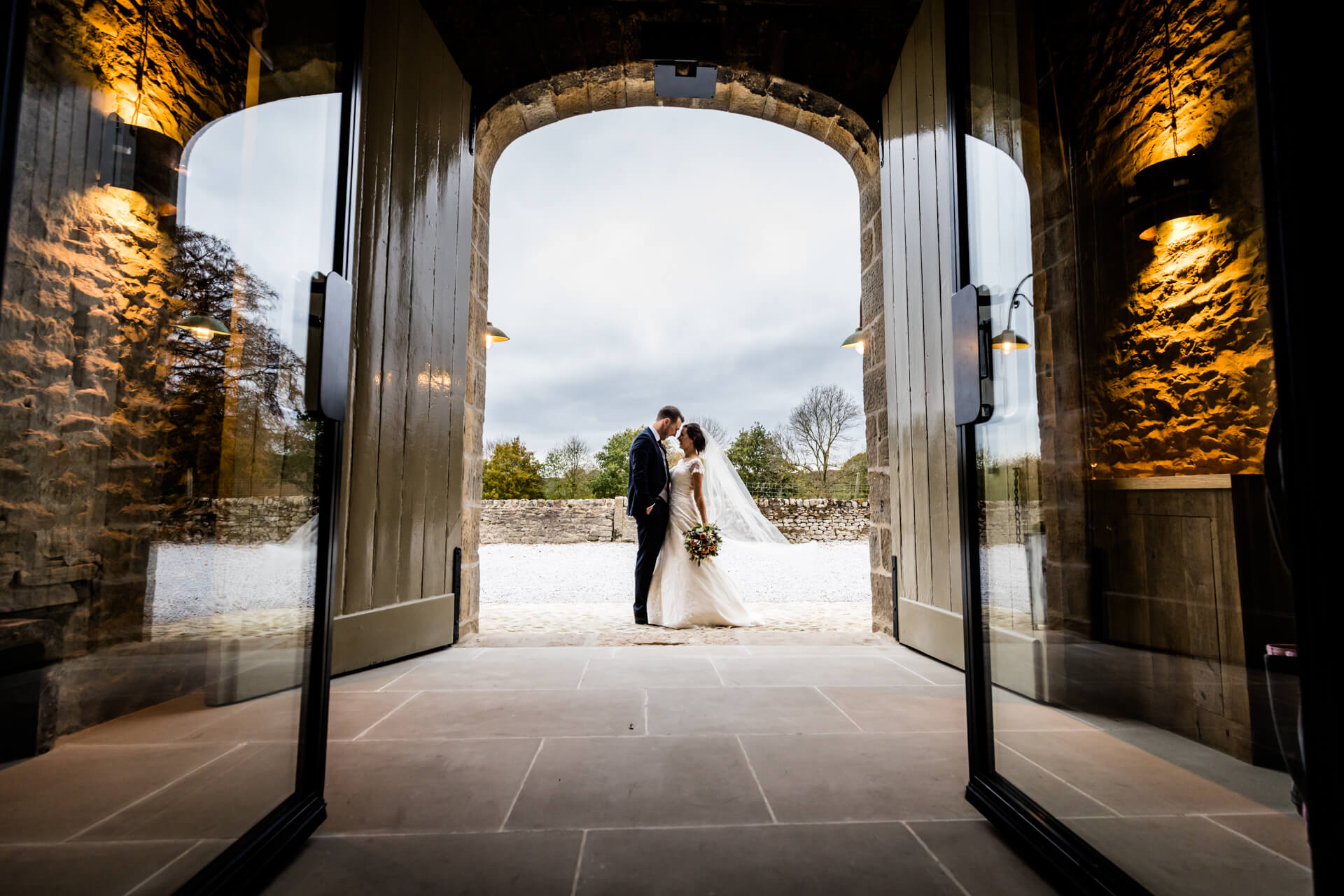 bride and groom in the archway of a wedding barn