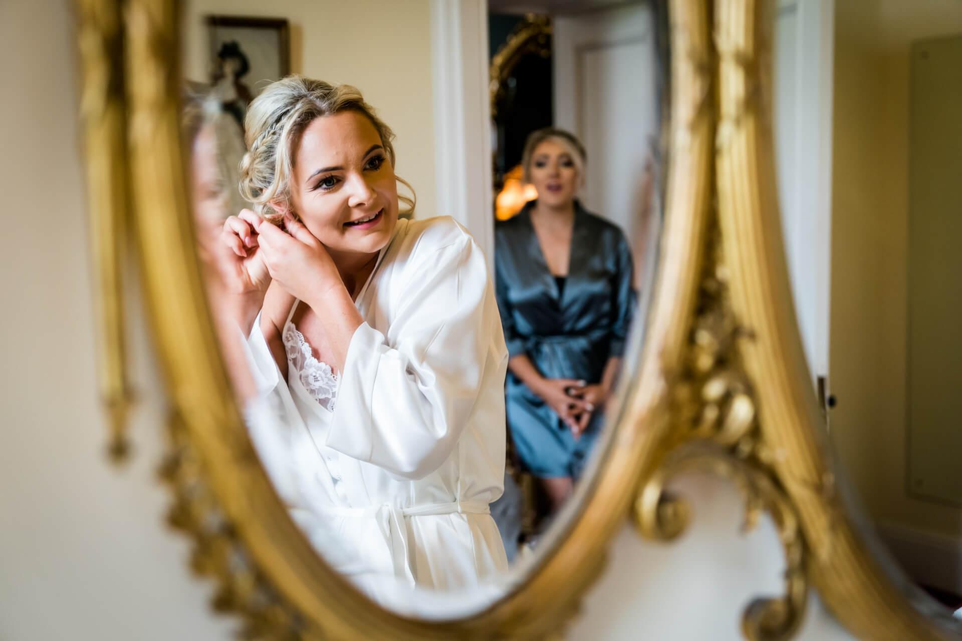 bride fixing her earrings in a mirror