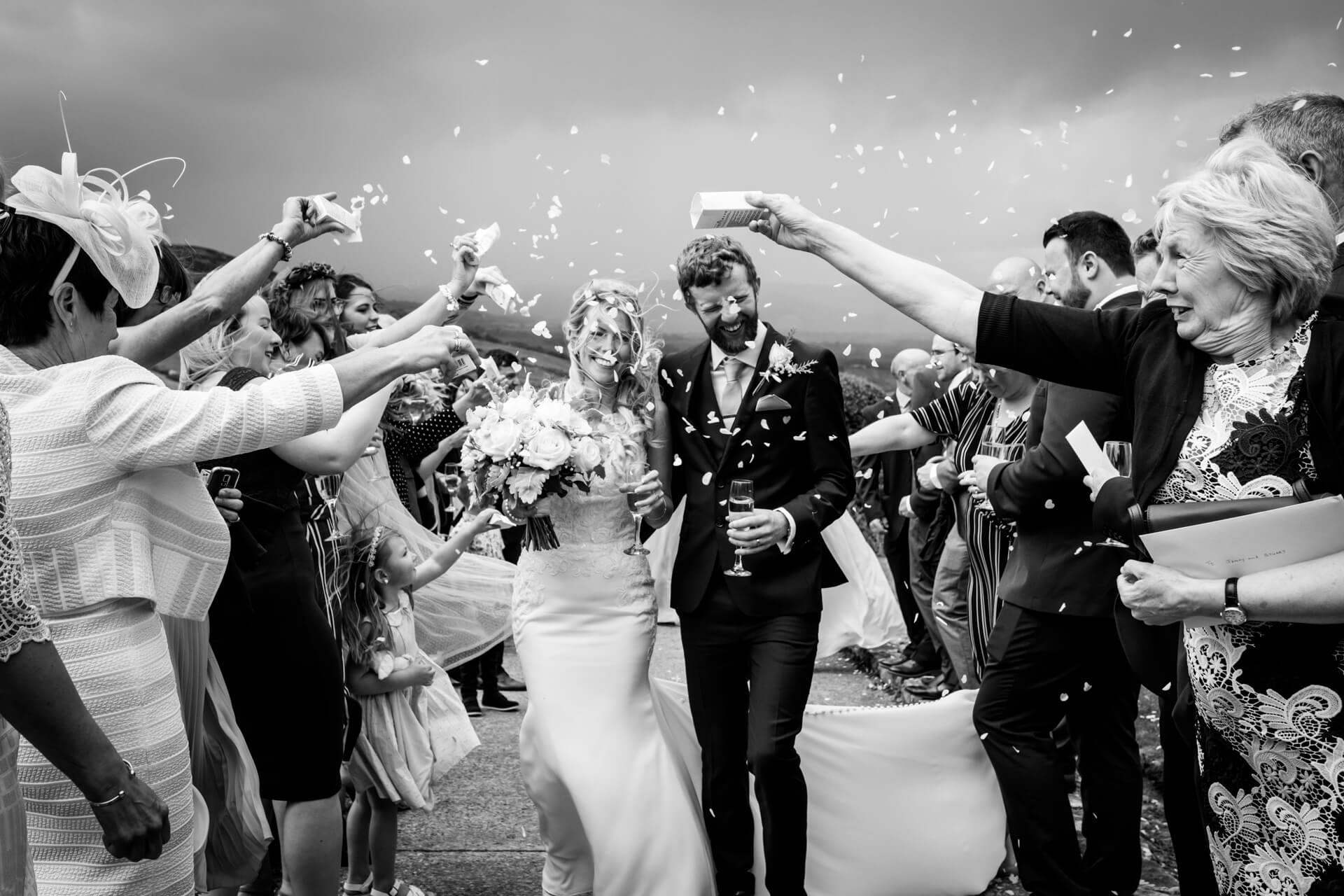 windblown wedding couple being showered with confetti
