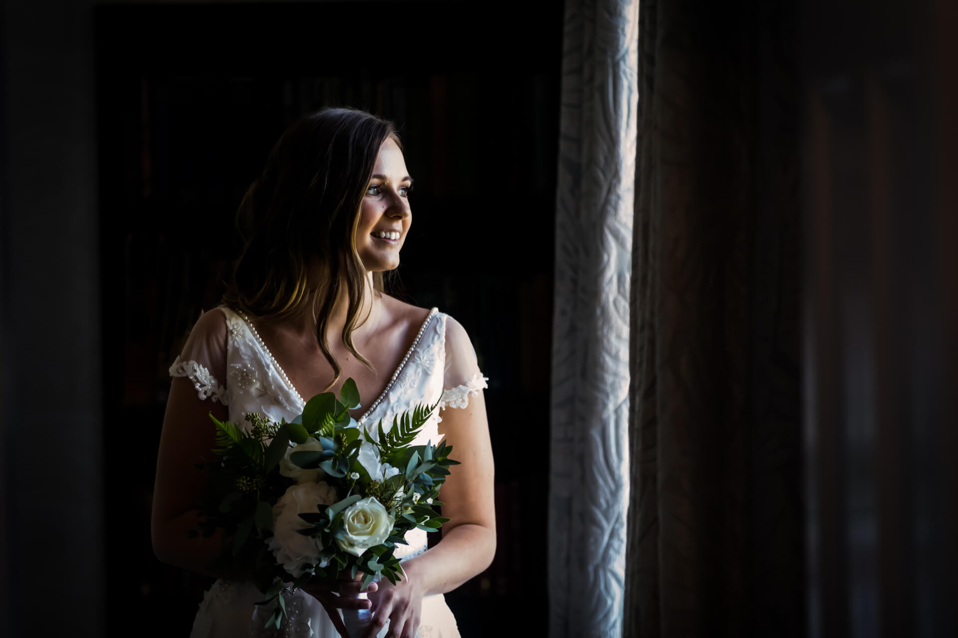 bride smiling and looking through a window