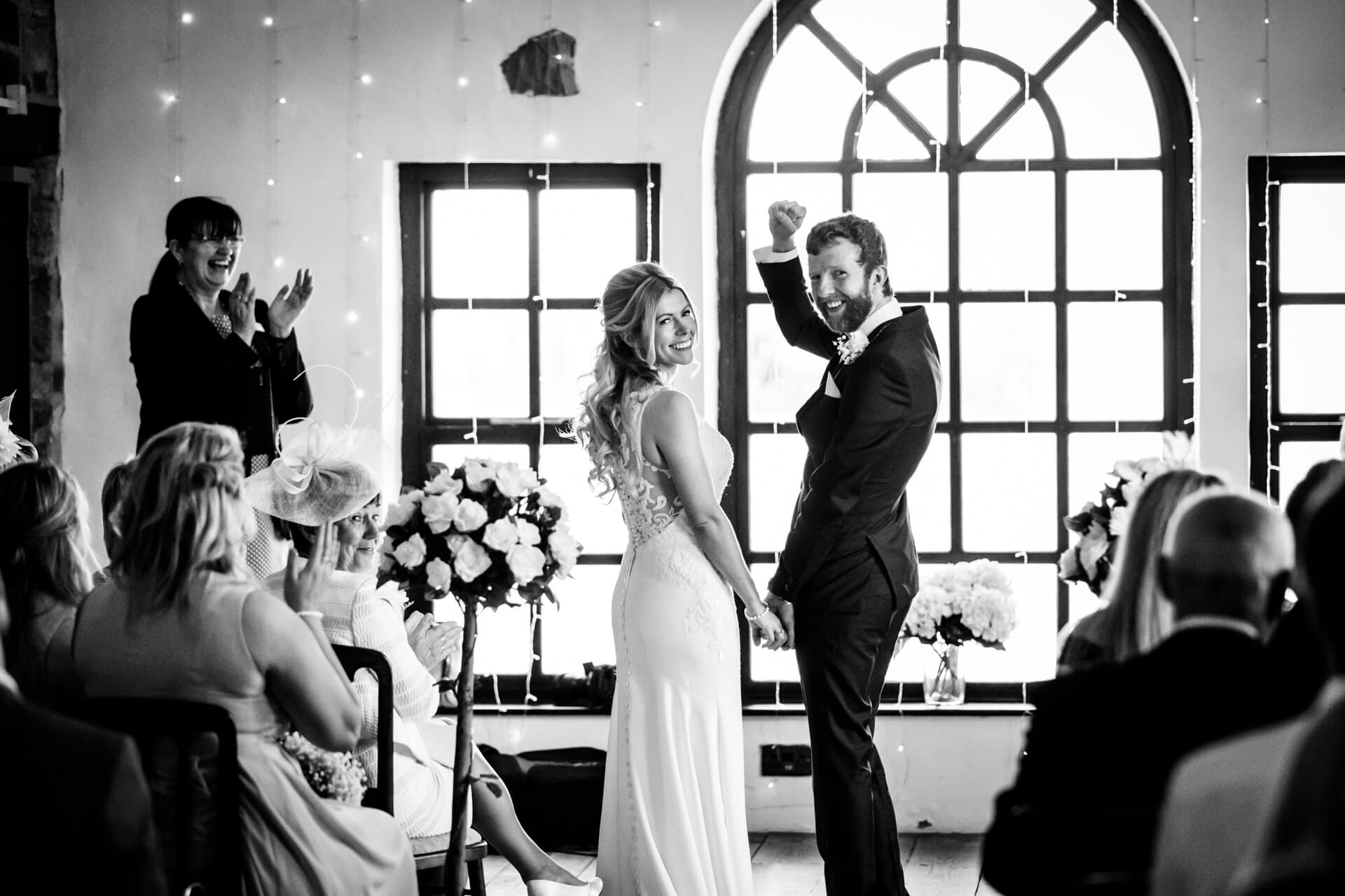 bride and groom smiling at their guests at the end of the ceremony