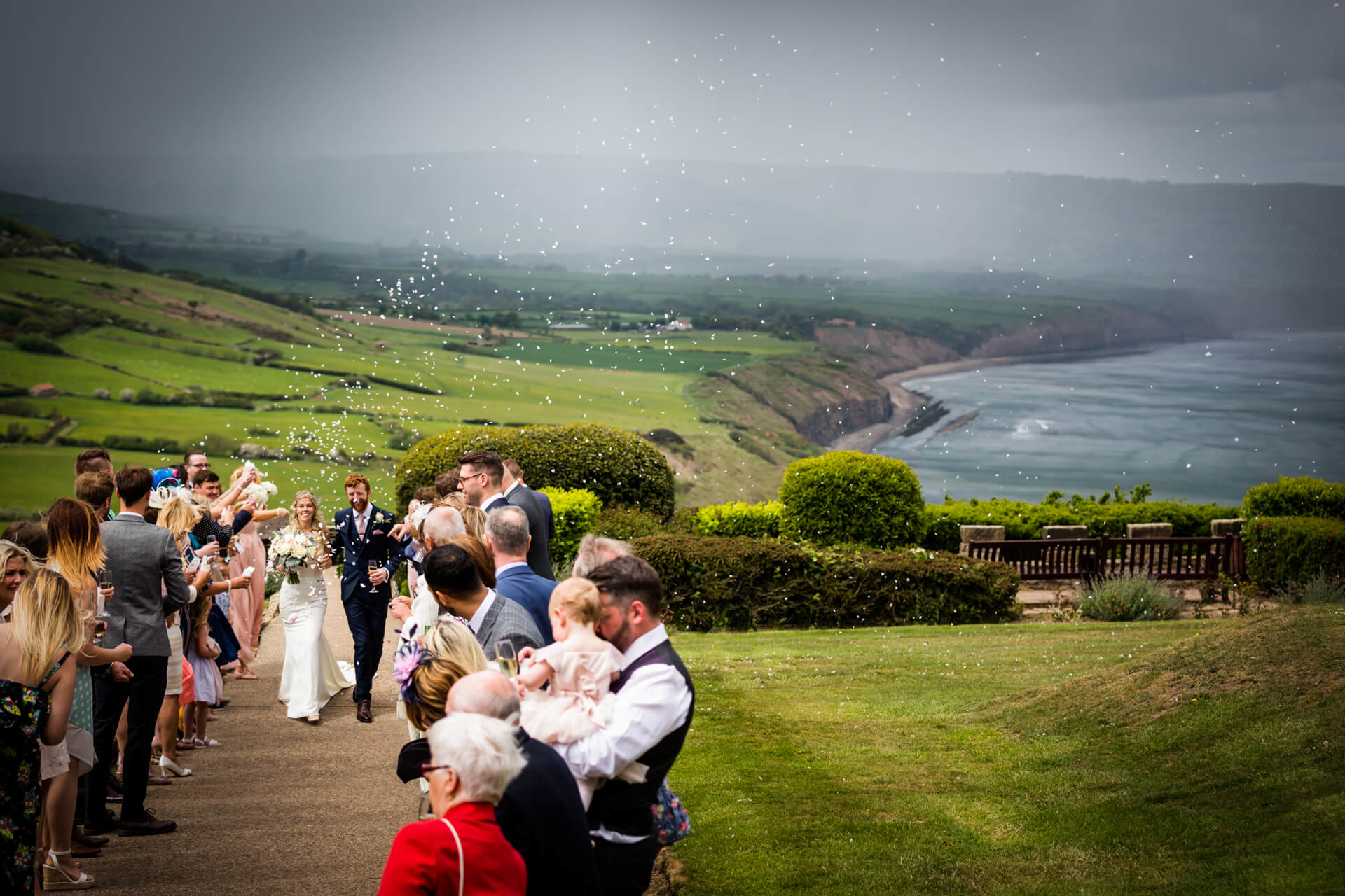 bride and groom walking through a confetti line in front of a dramatic coastal view