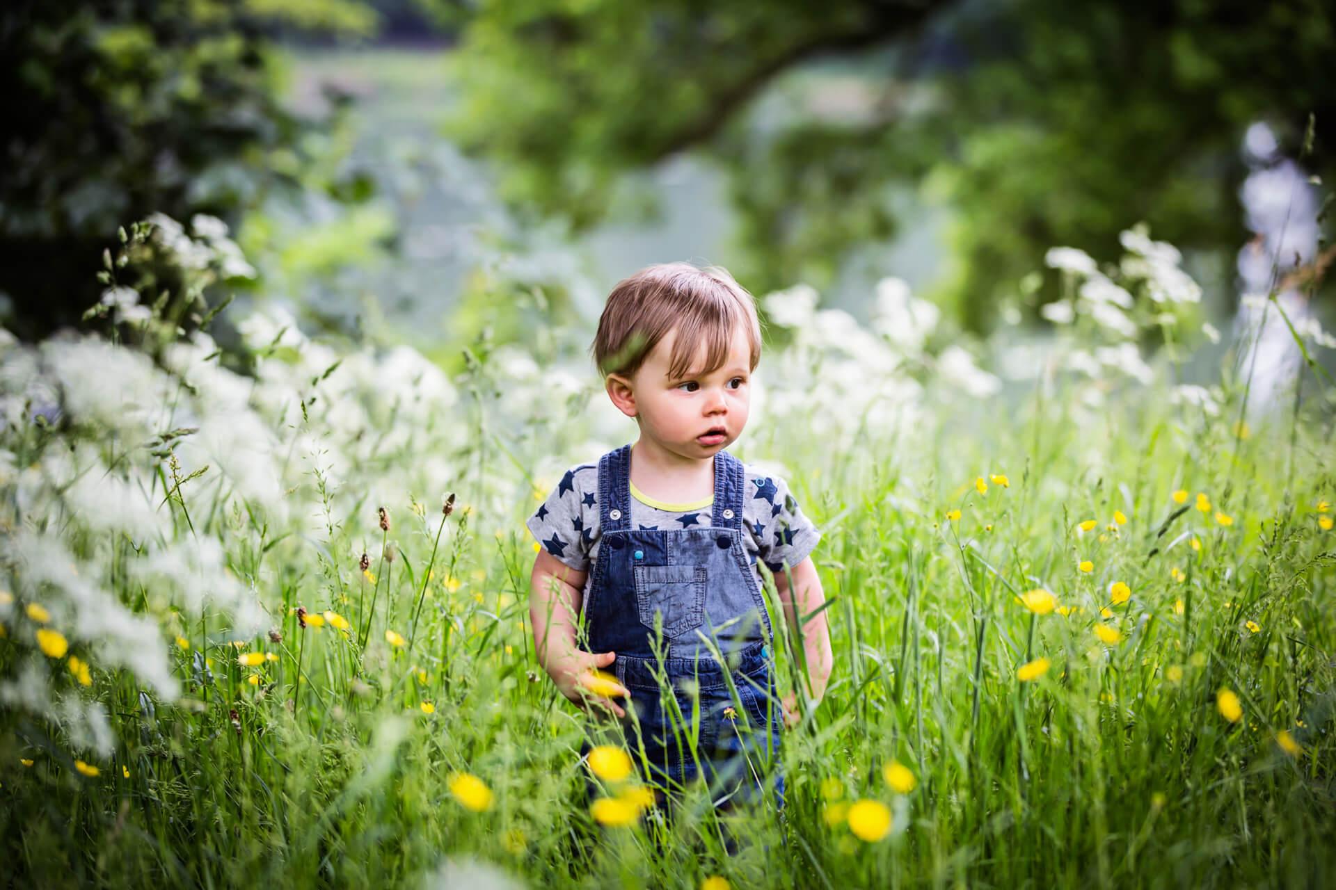 toddler walking in the long grass