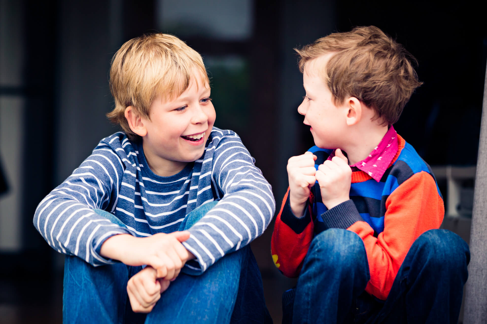 two boys chatting together whilst sitting in a doorway