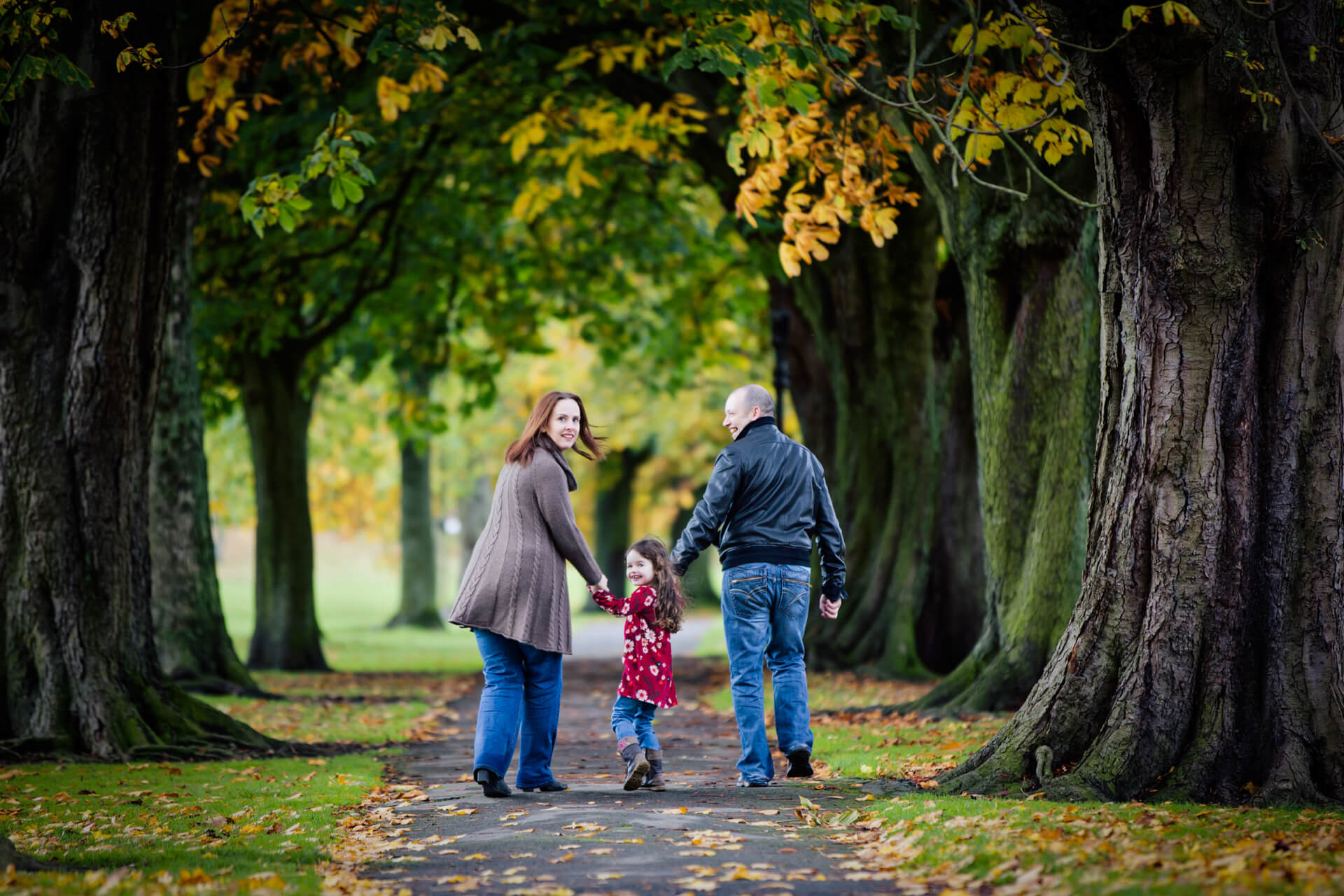parents with their toddler walking through a harrogate park