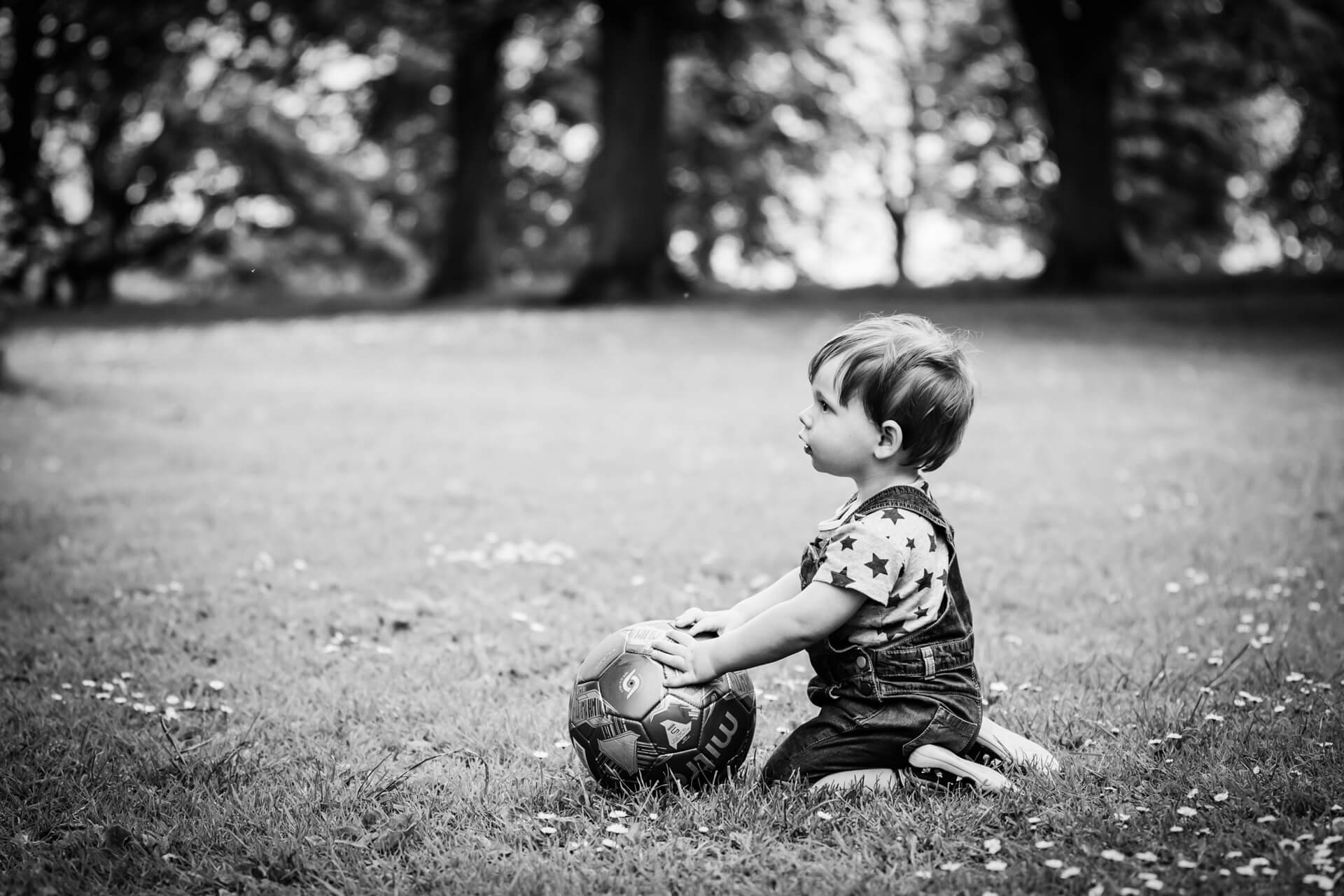 little boy sitting in Roundhay Park with his ball