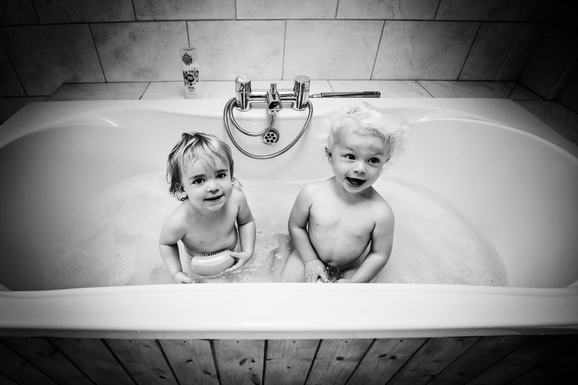 two small boys sitting in a bath