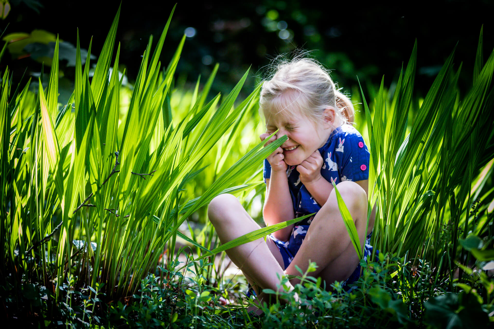 girl sitting in some long grass and laughing