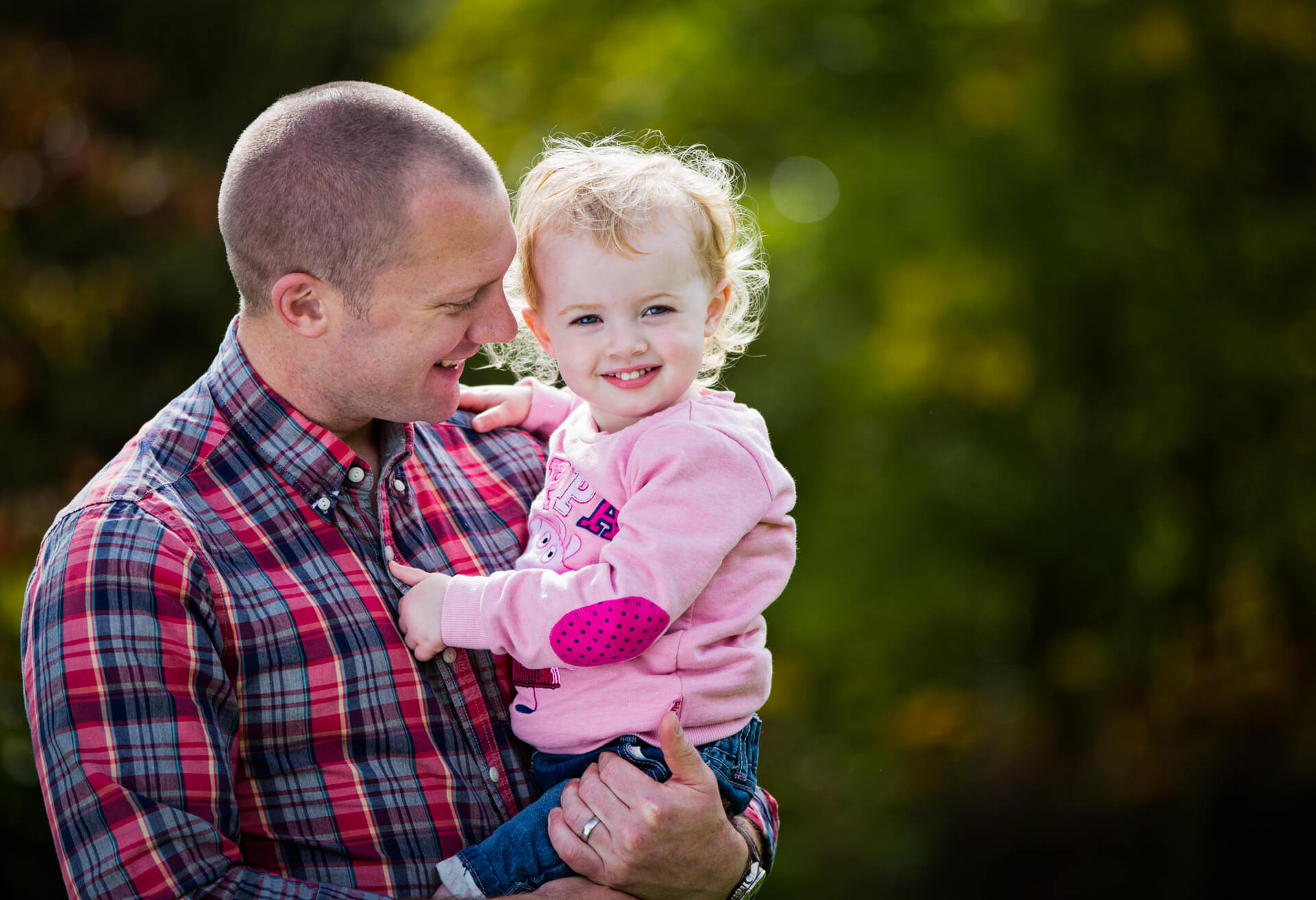 father smiling and holding his daughter
