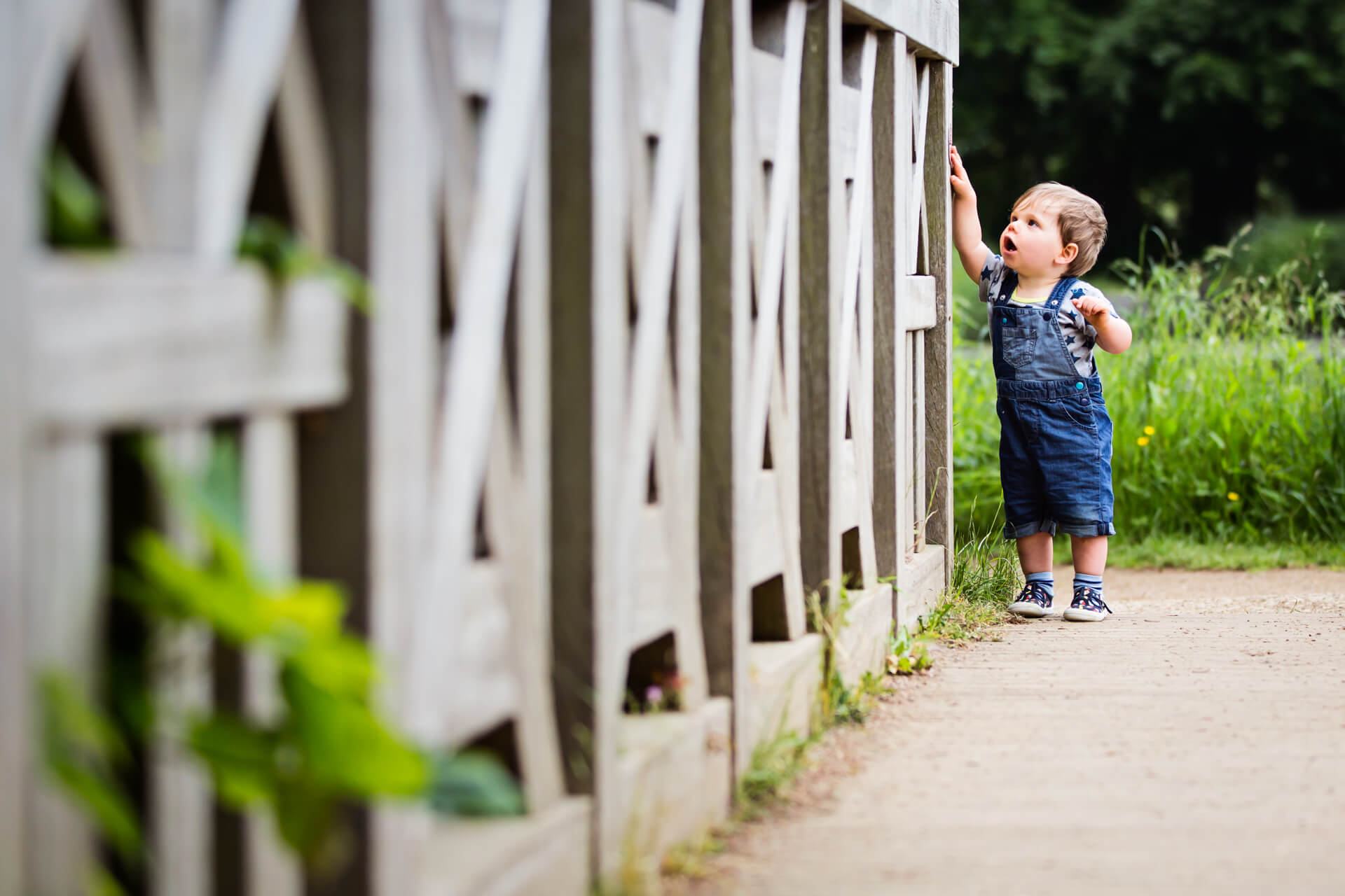 little boy standing at the end of a long fence