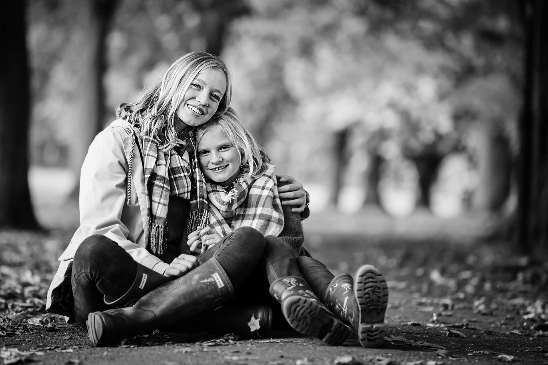 girl and her sister sitting in a park together