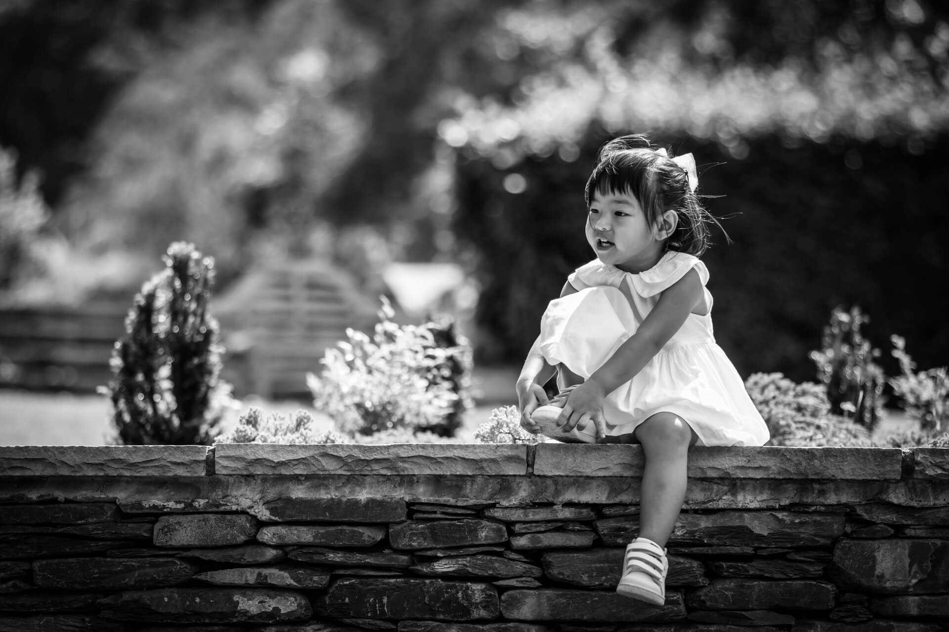 little girl sitting on a wall in a Lake district hotel garden